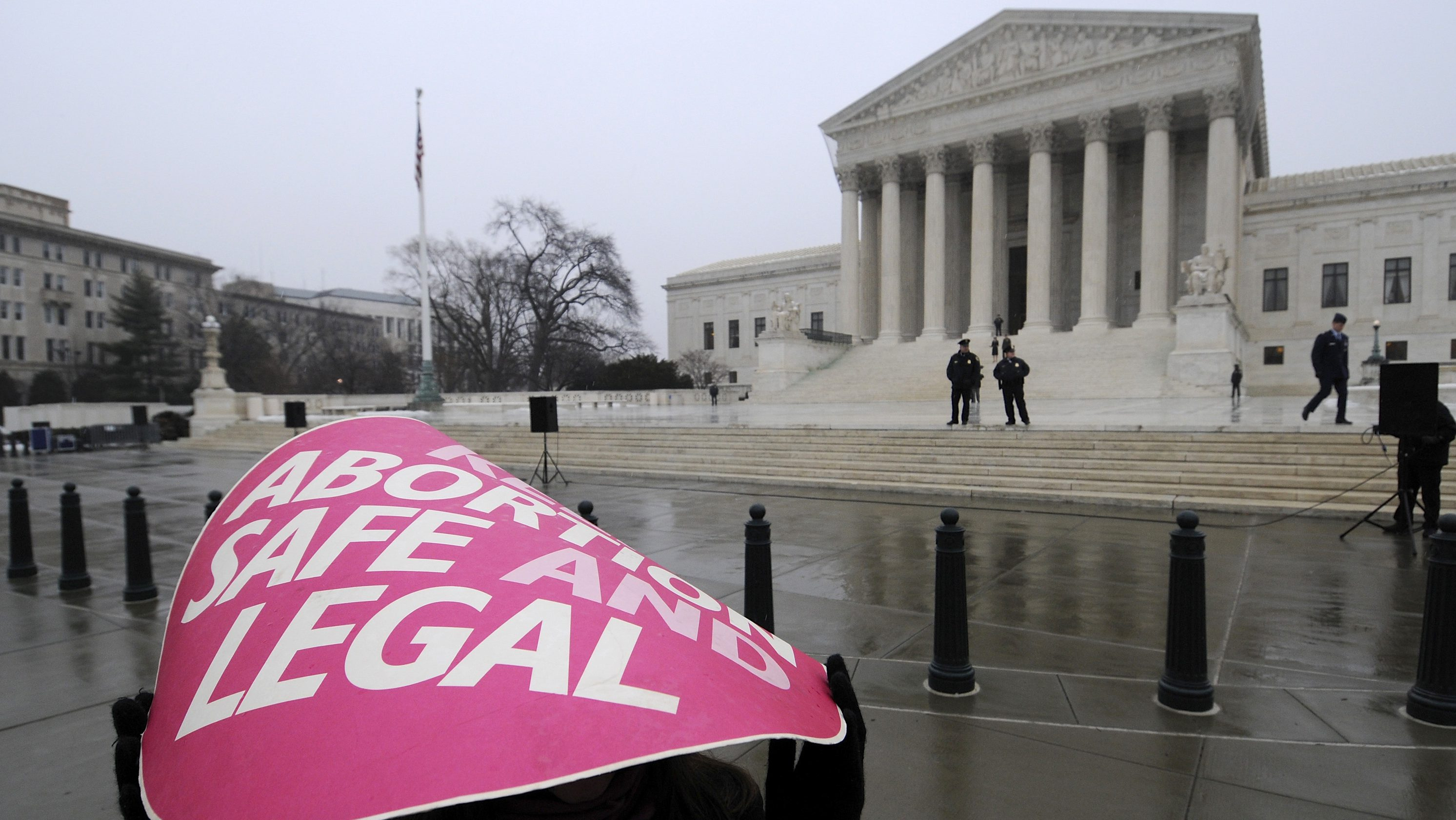 A woman holds a sign in the rain as abortion rights protestors arrive to prepare for a counter protest against March for Life anti-abortion demonstrators on the 39th anniversary of the Roe vs Wade decision, in front of the U.S. Supreme Court building in Washington, January 23, 2012. REUTERS/Jonathan Ernst   (UNITED STATES - Tags: POLITICS CIVIL UNREST HEALTH CRIME LAW) - GM1E81O03DT01