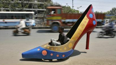 A worker test drives a car in the shape of a heels on a road in the southern Indian city of Hyderabad