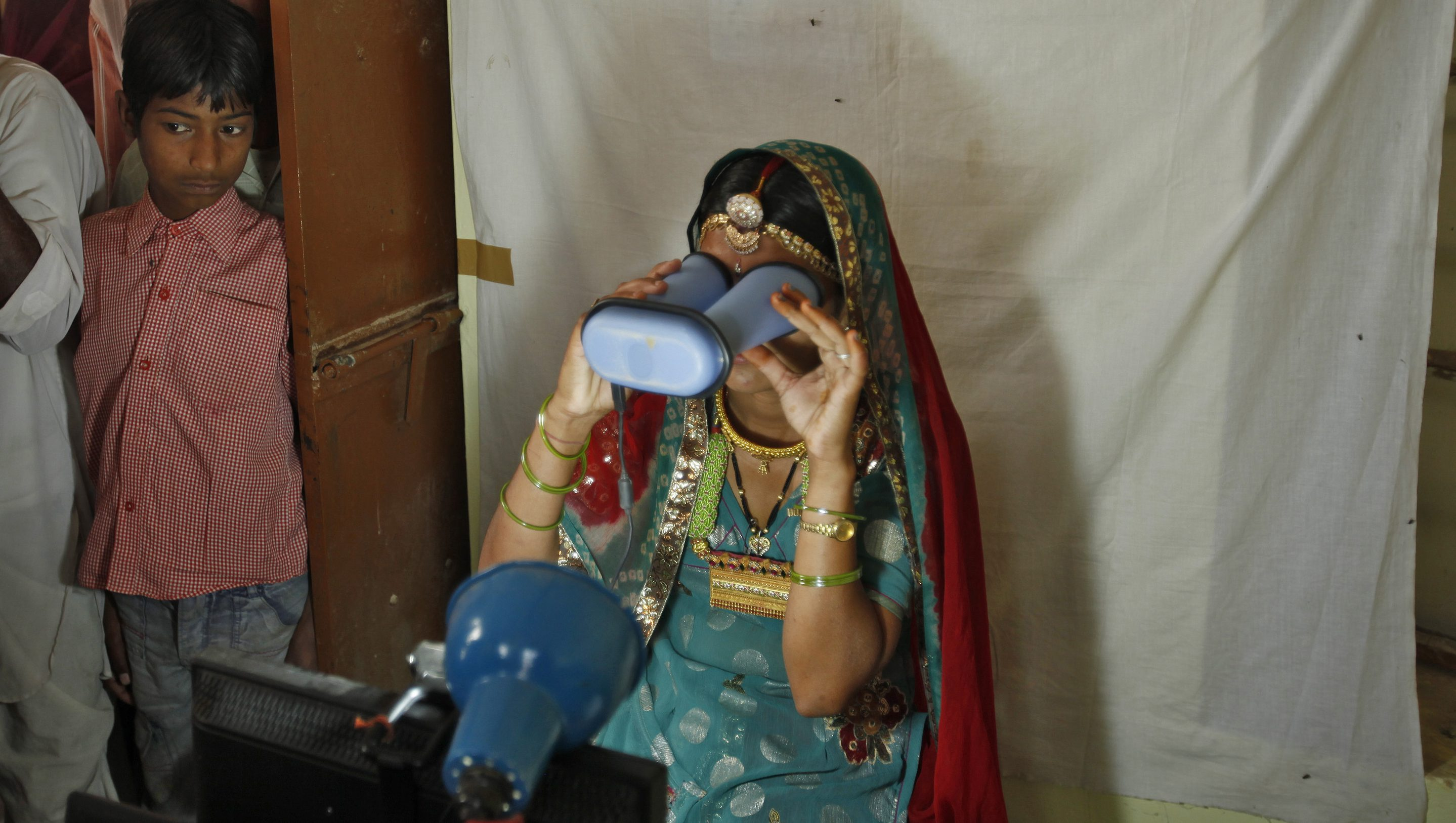A villager goes through the process of eye scanning for Unique Identification (UID) database system at an enrolment centre at Merta district in the desert Indian state of Rajasthan February 21, 2013.In a more ambitious version of programmes that have slashed poverty in Brazil and Mexico, the Indian government has begun to use the UID database, known as Aadhaar, to make direct cash transfers to the poor, in an attempt to cut out frauds who siphon billions of dollars from welfare schemes. Picture taken February 21, 2013. REUTERS/Mansi Thapliyal (INDIA - Tags: BUSINESS SOCIETY POVERTY SCIENCE TECHNOLOGY) - GM1E92S1B1001