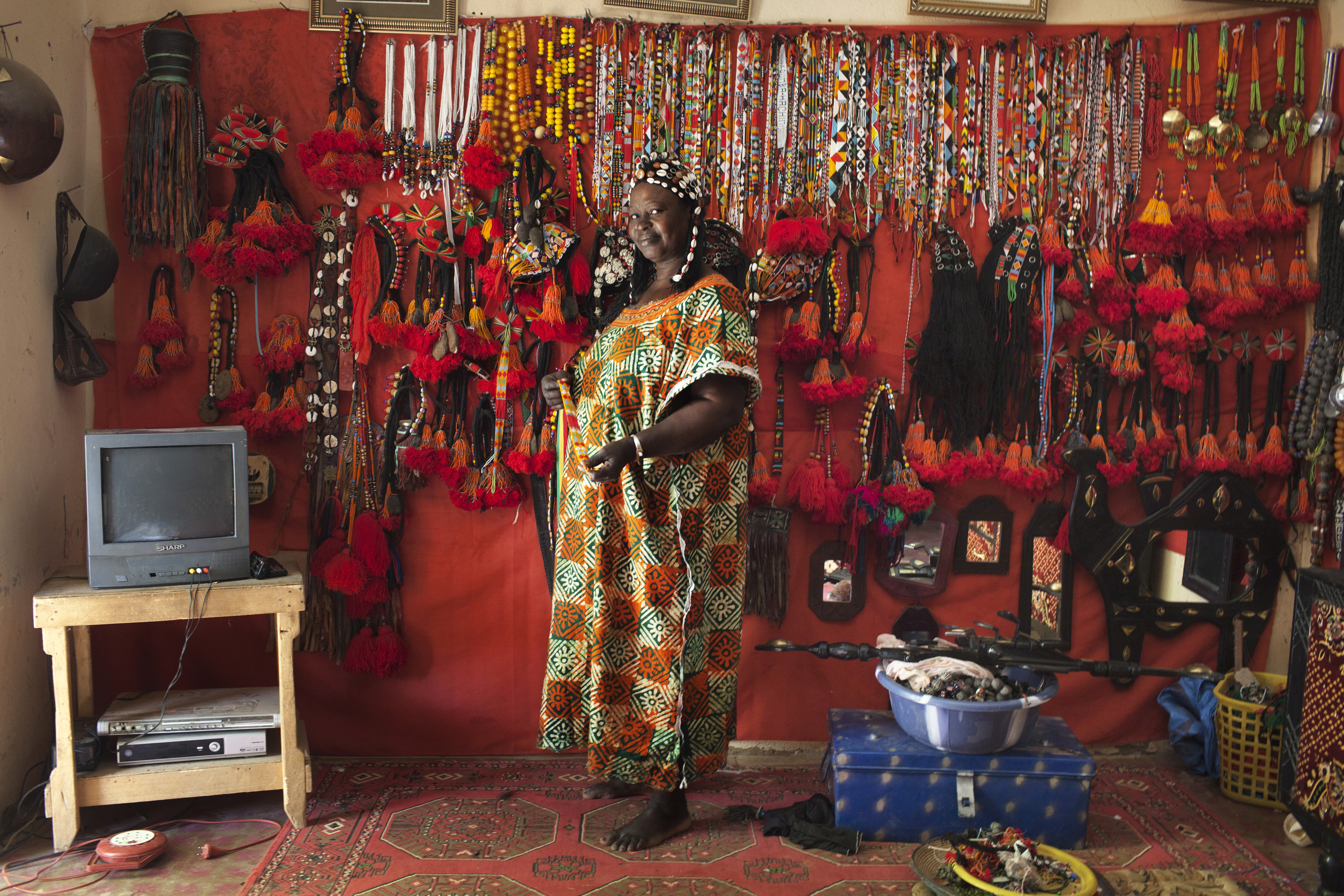 Hally Bara, an artisan, poses for a picture in front of traditional Songhai and Tuareg headdresses and jewelry she made at the store in her house in Gao, Mali, March 6, 2013. Radical Islamist group MUJAO placed limitations on the wearing of traditional women's headdresses during their nine-month reign in Gao, which ended in January with the arrival of French and Malian troops. The headdresses, made of beads, gemstones, fabric and fake hair and traditionally worn by elites for special occasions, were criticised by MUJAO who said they were not Islamic enough. Issues surrounding the treatment of women are receiving special attention on March 8, which marks International Women's Day. Picture taken March 6, 2013. REUTERS/Joe Penney (MALI - Tags: SOCIETY RELIGION)  ATTENTION EDITORS: PICTURE 16 OF 16 FOR PACKAGE 'HEADDRESSES OF GAO'. SEARCH 'HEADDRESSES PENNEY' FOR ALL IMAGES - GM1E9381BSB01