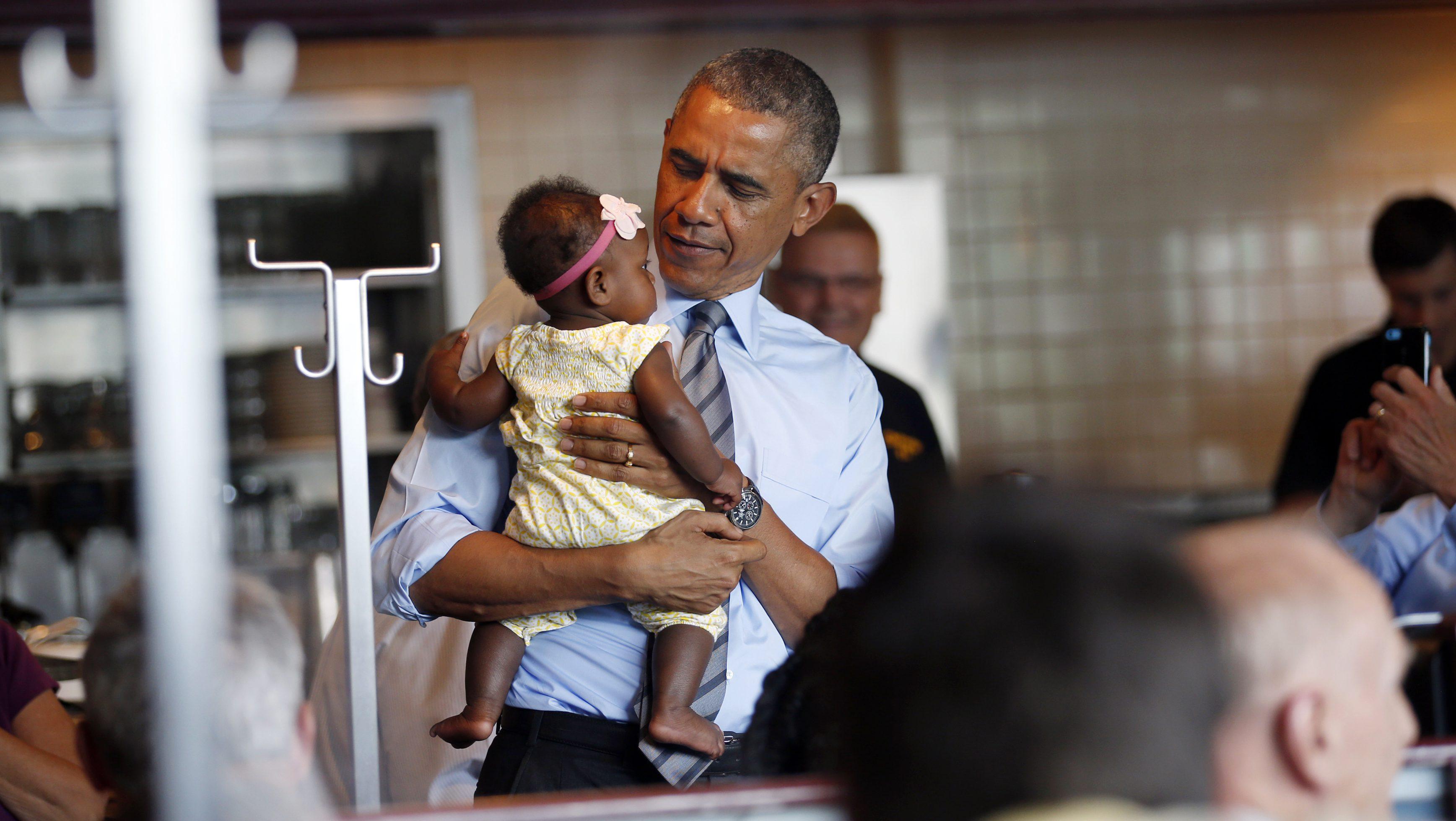 Barack Obama holding a baby.