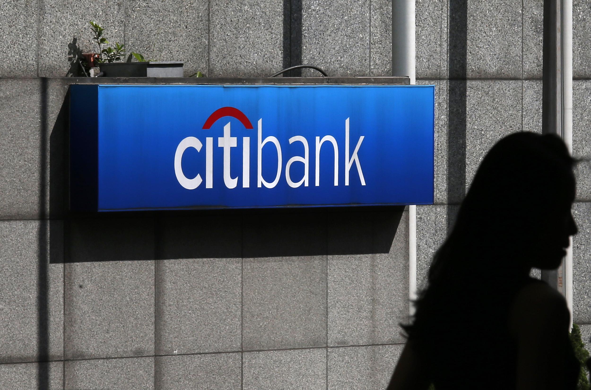 A woman walks past a Citibank logo