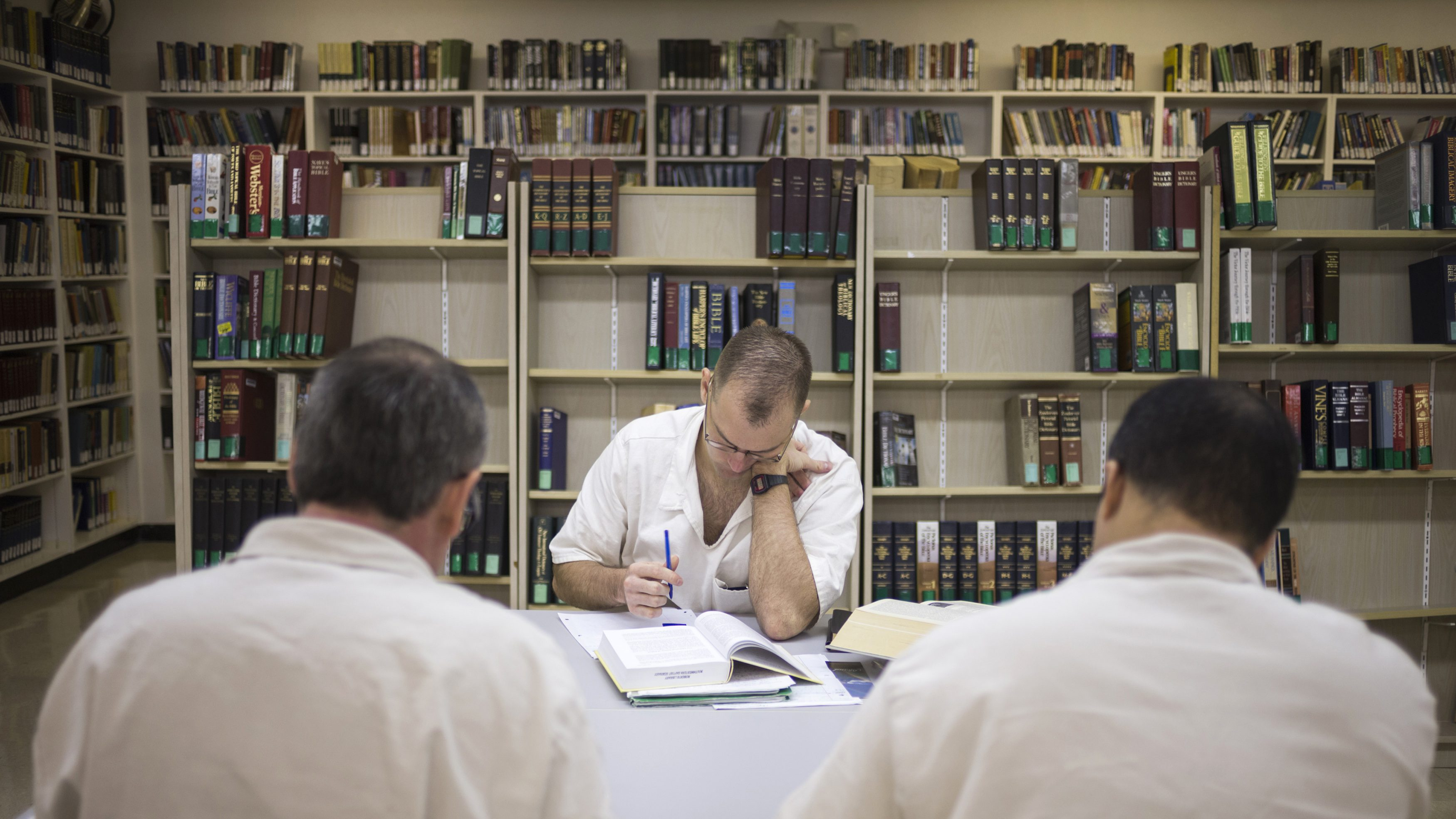 Offenders read and write papers inside the Southwestern Baptist Theological Seminary library located in the Darrington Unit of the Texas Department of Criminal Justice men's prison in Rosharon, Texas August 12, 2014. The Southwestern Baptist Theological Seminary, a private college based in Fort Worth, Texas, began its bachelor of science in biblical studies program at Darrington, south of Houston, about three years ago. To be accepted, an offender has to be at least 10 years from the possibility of parole, have a good behavior record and the appropriate academic credentials to enroll in a college course. The program, which is largely paid for by charitable contributions from the Heart of Texas Foundation, has more than 150 prisoners enrolled and plans to send its graduates as field ministers to other units who want the bible college alumni for peer counseling and spiritual guidance. The first degrees are expected to be conferred next year. Picture taken August 12, 2014. To match Feature USA-TEXAS/PRISON      REUTERS/Adrees Latif (UNITED STATES - Tags: CRIME LAW EDUCATION SOCIETY RELIGION) - GM1EA8G01OP01