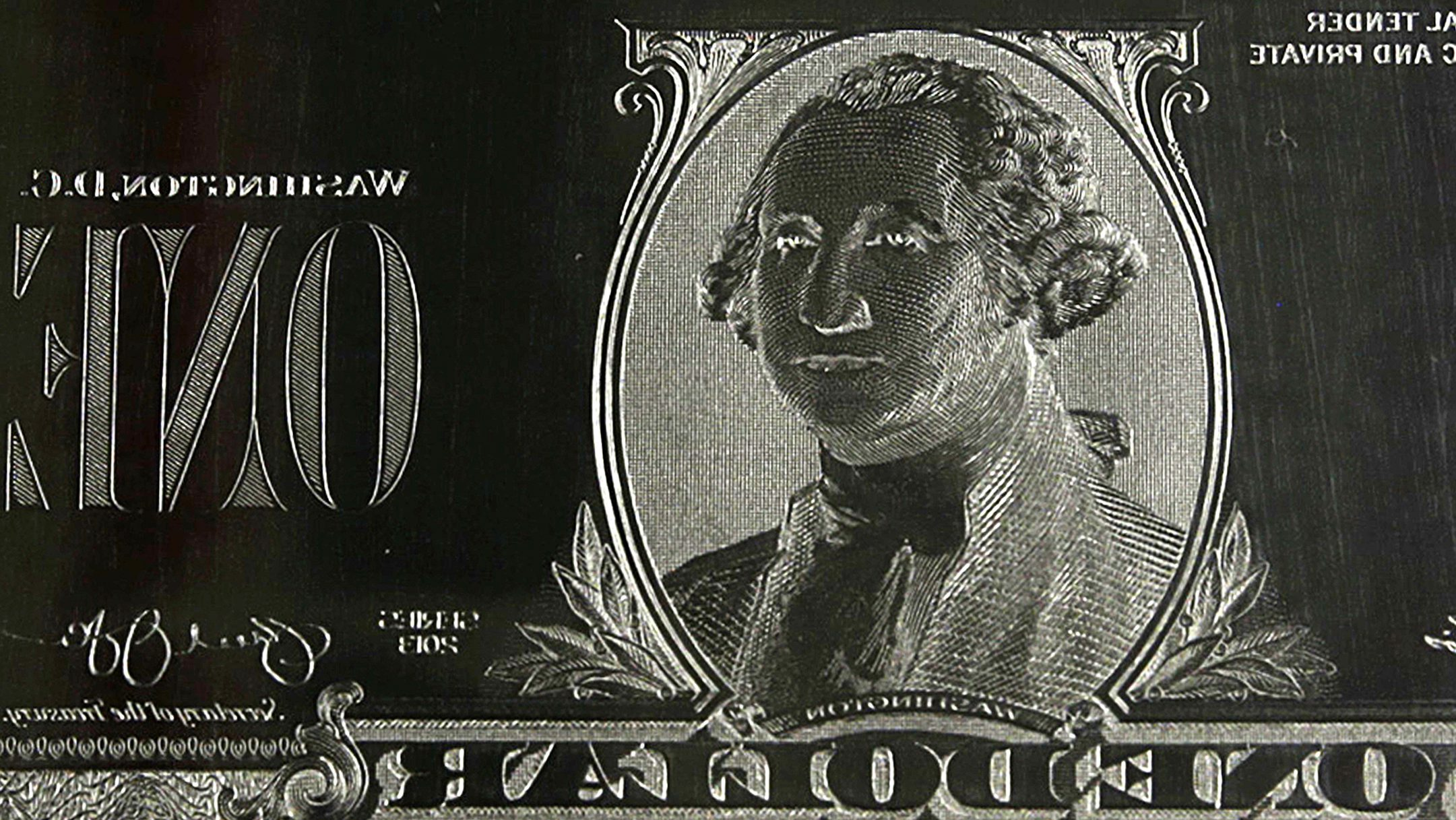 The image of United States President George Washington is seen on an engraving plate for a US one dollar bill at the Bureau of Engraving and Printing in Washington November 14, 2014. The plate goes on the printing press which prints the currency. The dollar gave up strong early gains to turn lower on Friday after the battered euro turned higher on reports of short-covering in the common currency and a drop in U.S. bond yields.  REUTERS/Gary Cameron    (UNITED STATES - Tags: BUSINESS POLITICS TPX IMAGES OF THE DAY) - TM3EABE14WS01