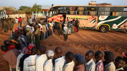 Passengers travelling to Nairobi stand in front of a bus, as they wait to be searched for weapons by Kenyan police, in the town of Mandera at the Kenya-Somalia border December 8, 2014.
