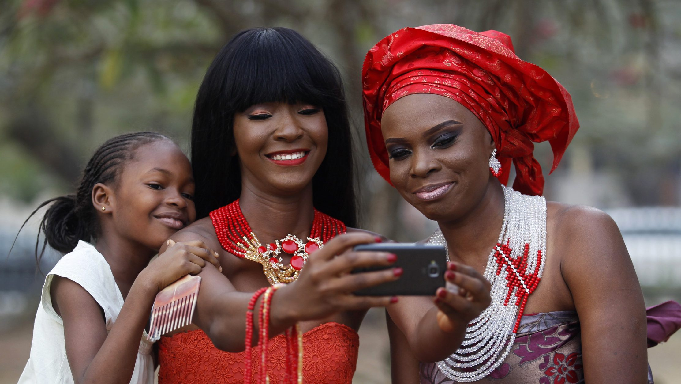 Models take selfies as they display neck beads, popularly used in social ceremonies, at a park in Ikeja duistrict in Lagos January 11, 2015.