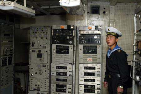 A North Korean navy soldier stands guard at a communication room in the United States' navy spy ship USS Pueblo on a river in Pyongyang May 3, 2004. The spy ship was seized by the North Korean navy with 83 crew in 1968. The 82 survivors were freed after nearly a year of tense negotiations. About 300 South Korean workers completed on Monday a four-day trip to Pyongyang for an inter-Korean May Day celebration.