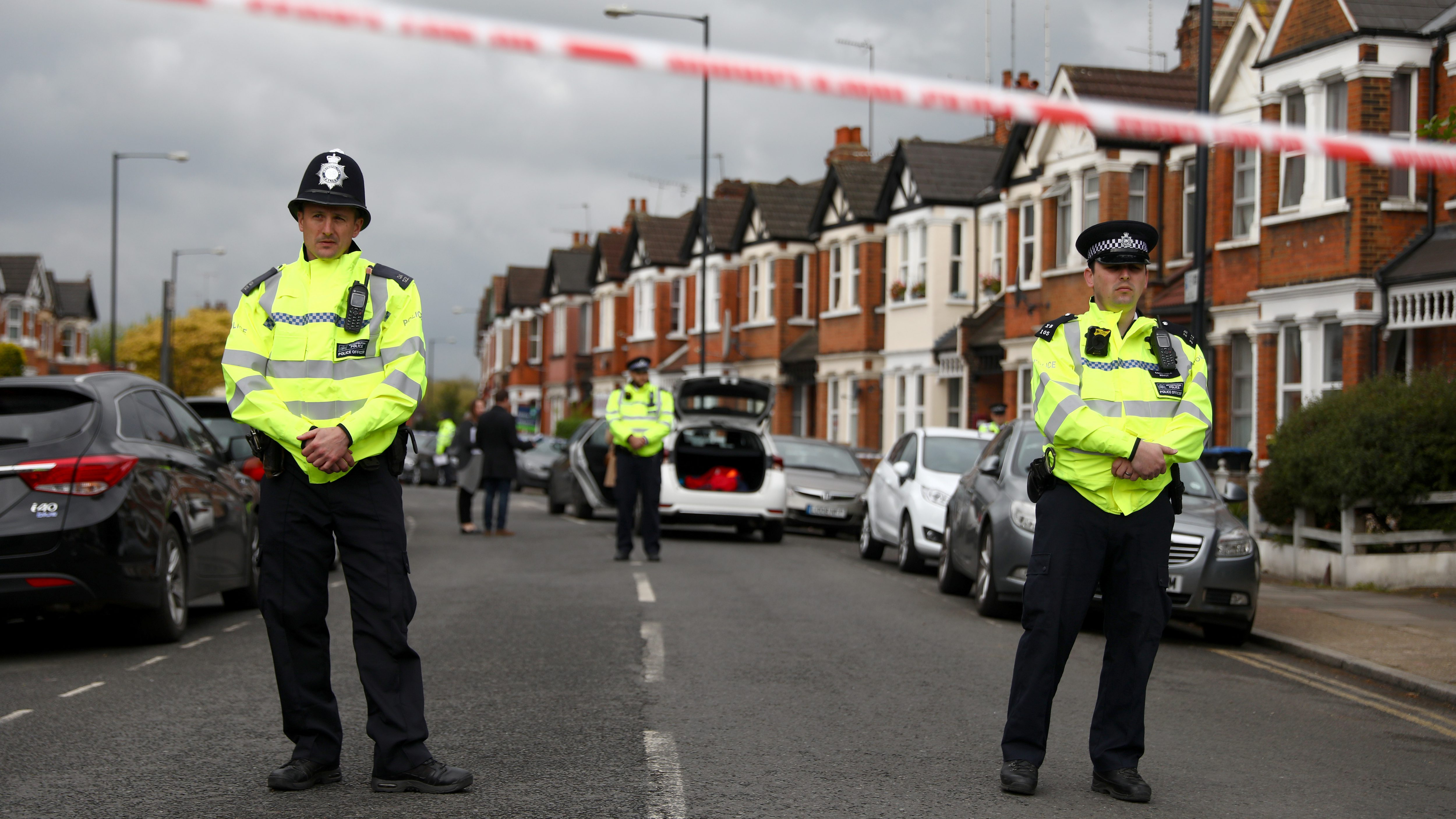 Police officers stand next to terraced housing in Harlesden Road, north London