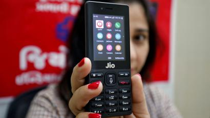 A sales person displays JioPhone as she poses for a photograph at a store of Reliance Industries' Jio telecoms unit, on the outskirts of Ahmedabad