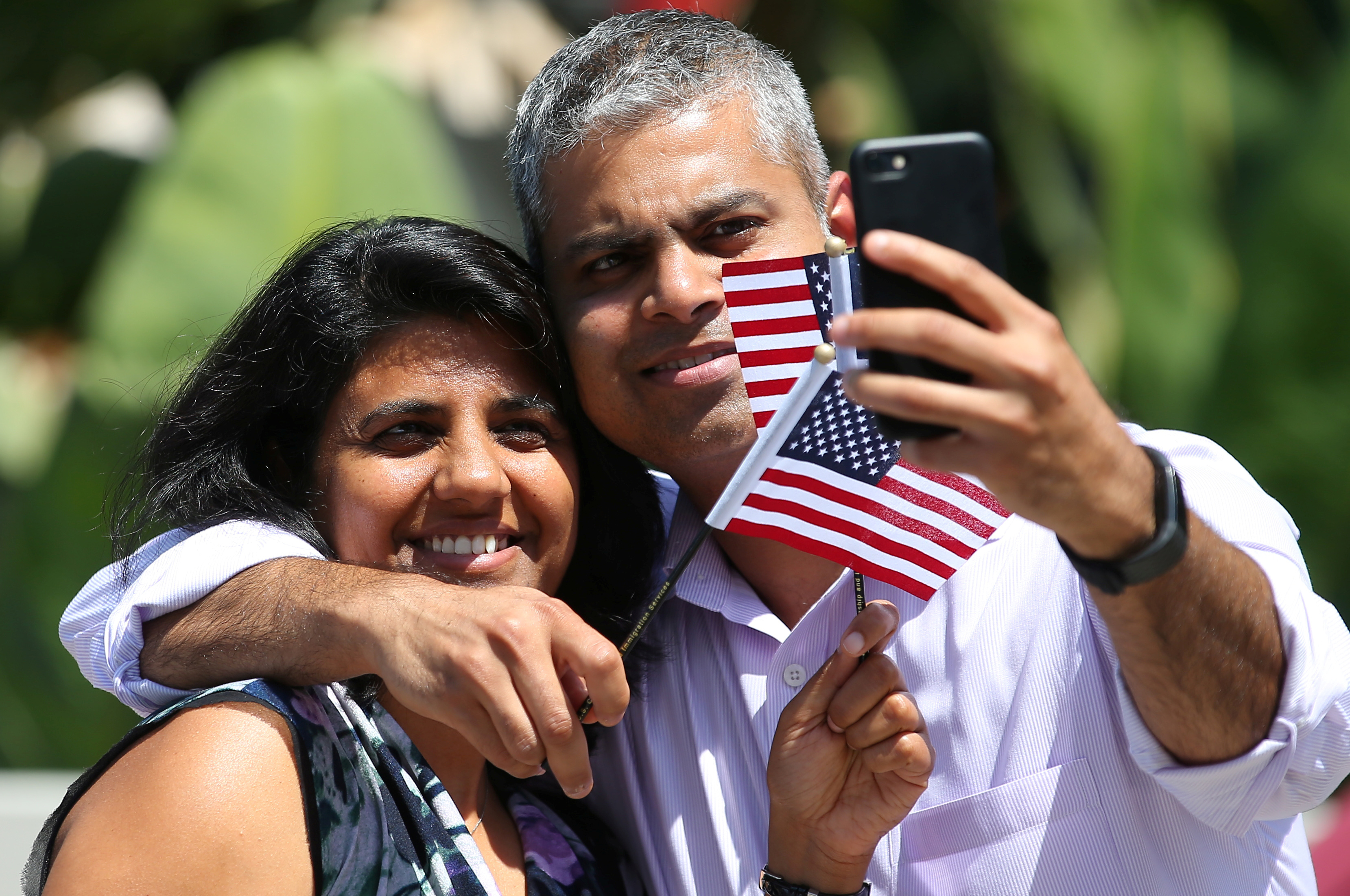 Newly naturalized U.S. citizens take a selfie after attending their citizenship ceremony in Los Angeles, U.S., July 18, 2017. Picture taken July 18, 2017.     REUTERS/Mike Blake - RC18615CFD80