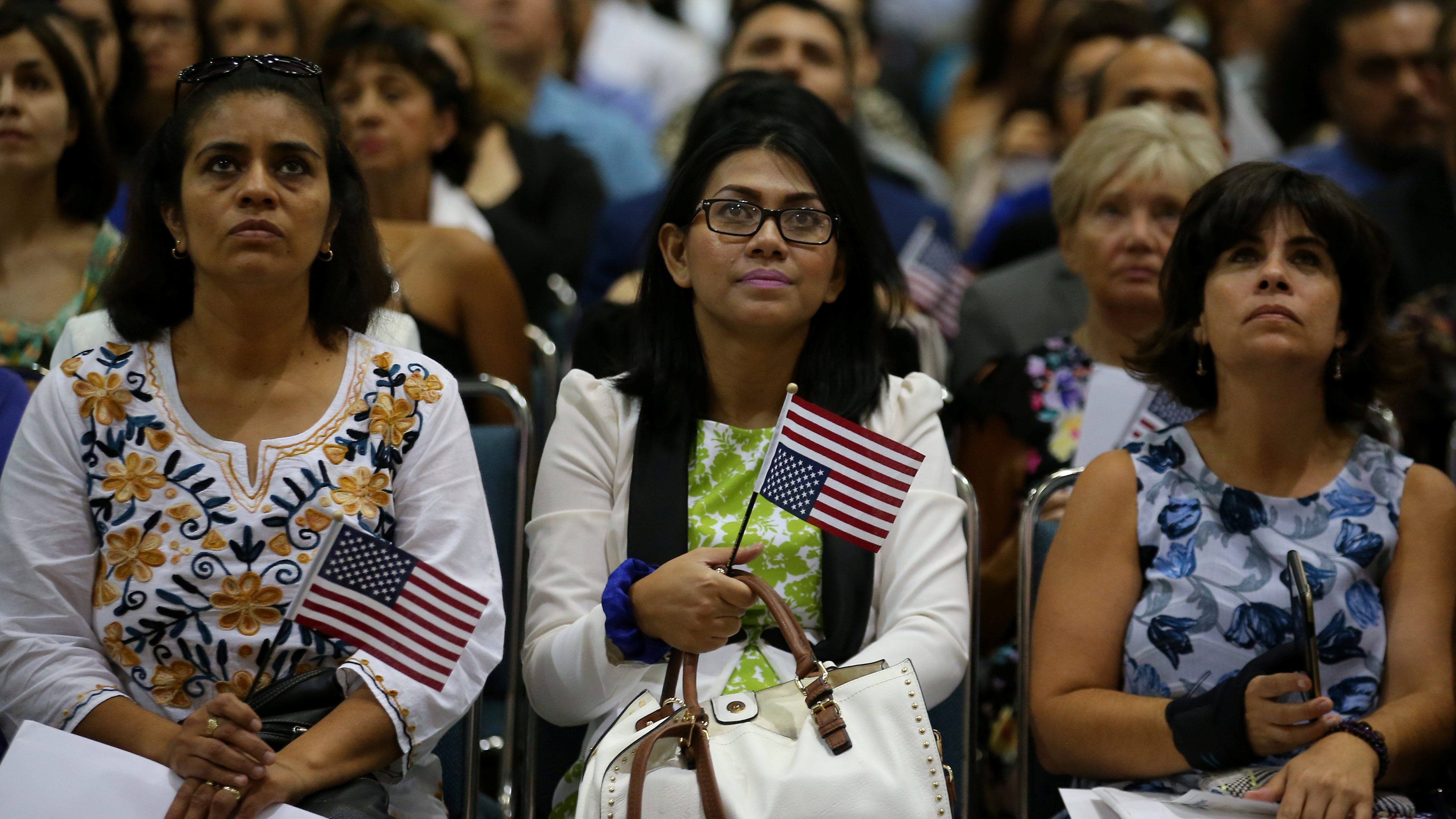 Attendees watch a video as they are sworn in as U.S. citizens at a U.S. citizenship ceremony in Los Angeles, U.S., July 18, 2017. Picture taken July 18, 2017.     REUTERS/Mike Blake - RC19F6476A60