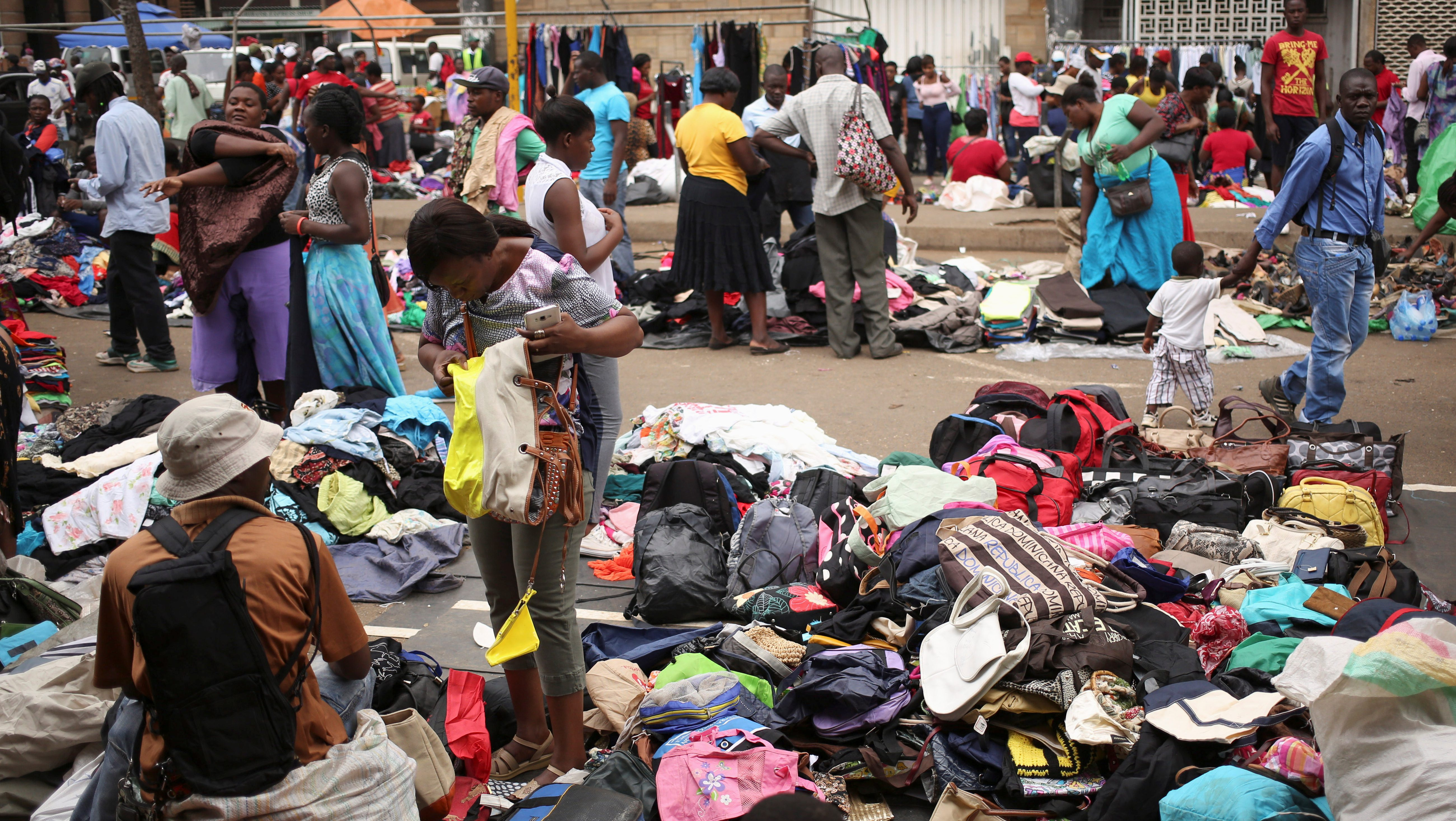 A shopper browses used clothings and bags at a market in Harare, Zimbabwe