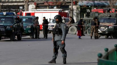 An Afghan policeman keeps watch at the site of today's car bomb attack in Kabul.