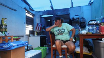 Morales sits in her kitchen without power and with a plastic sheet replacing the roof, in Yabucoa