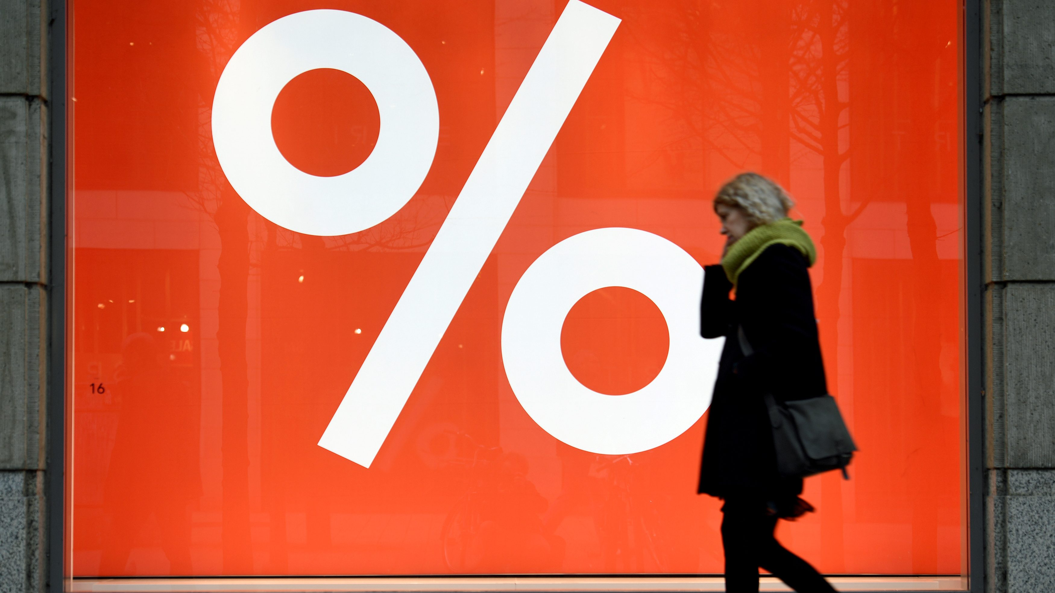 A woman passes a sale sign in a shop window in downtown Hamburg, Germany, January 25, 2018. REUTERS/Fabian Bimmer/File Photo - RC17D0C003A0