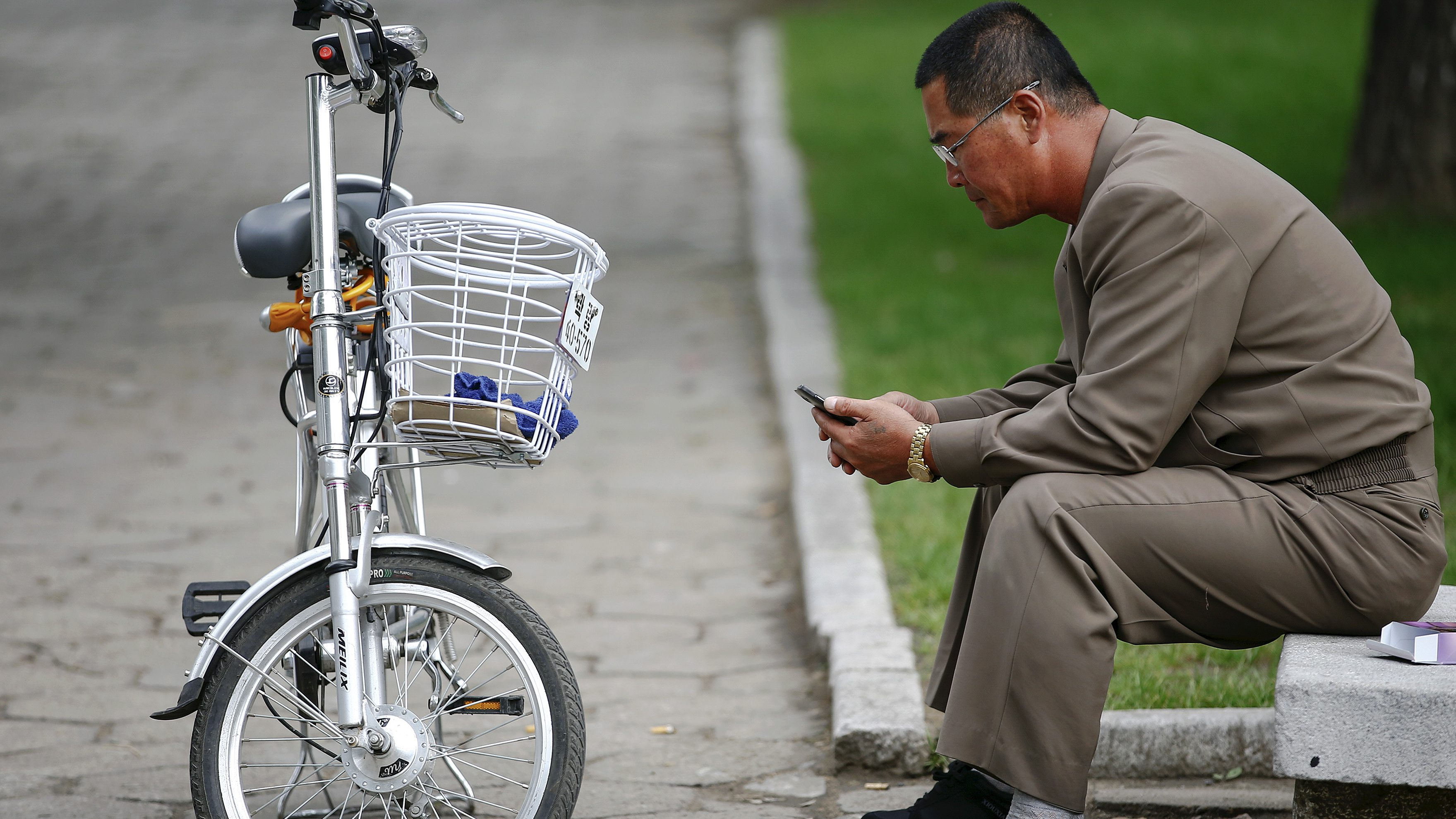 A man uses his mobile phone next to an electric bicycle in downtown Pyongyang