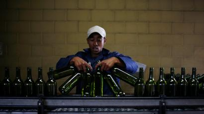 A worker loads wine bottles onto a conveyer belt at the Rostberg bottling plant near Cape Town, November 29, 2012.