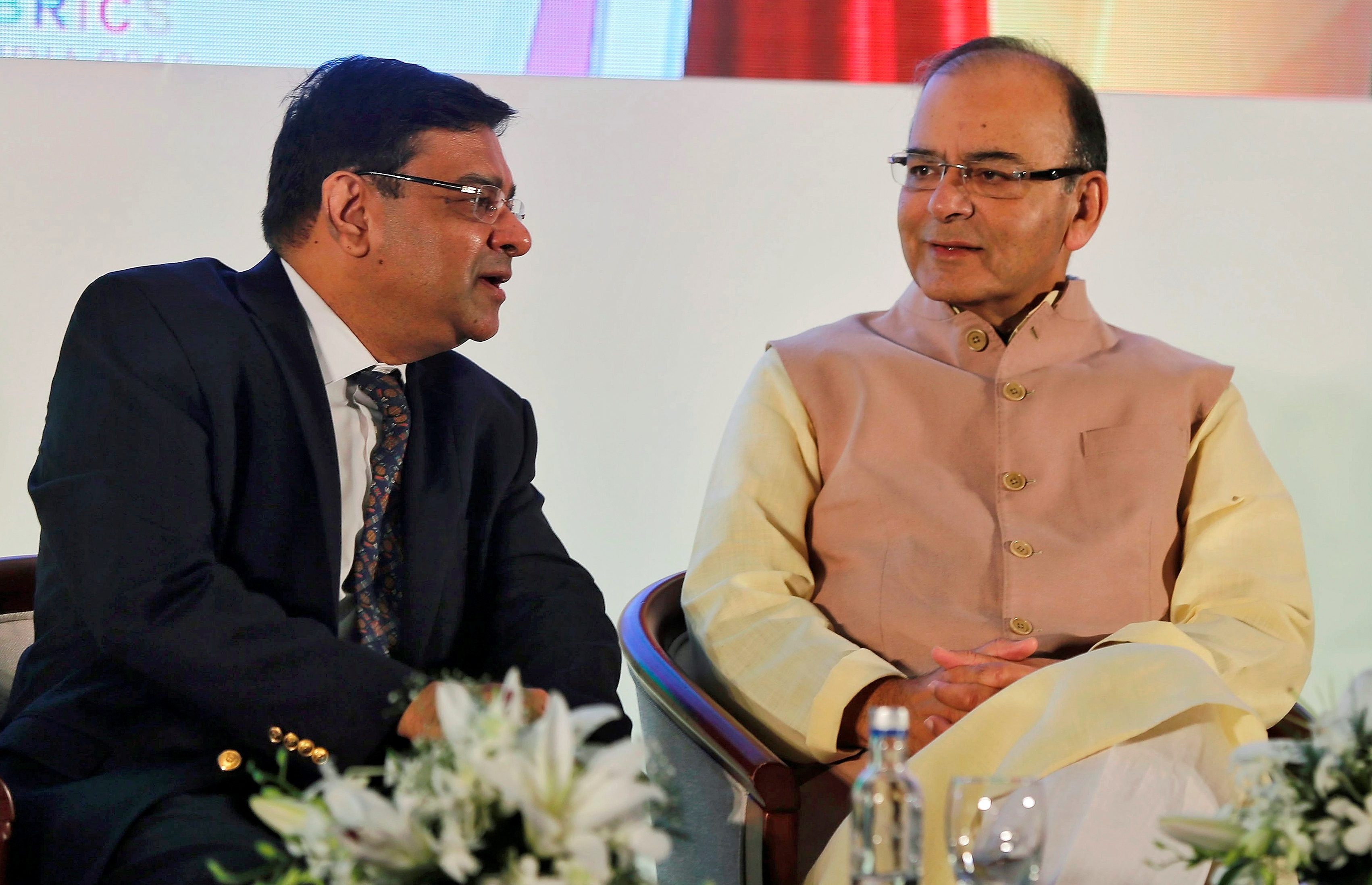 The Reserve Bank of India (RBI) Governor Urjit Patel speaks with India's Finance Minister Arun Jaitley (R) at a seminar in Mumbai, India, October 13, 2016.  - S1BEUGSJAZAA