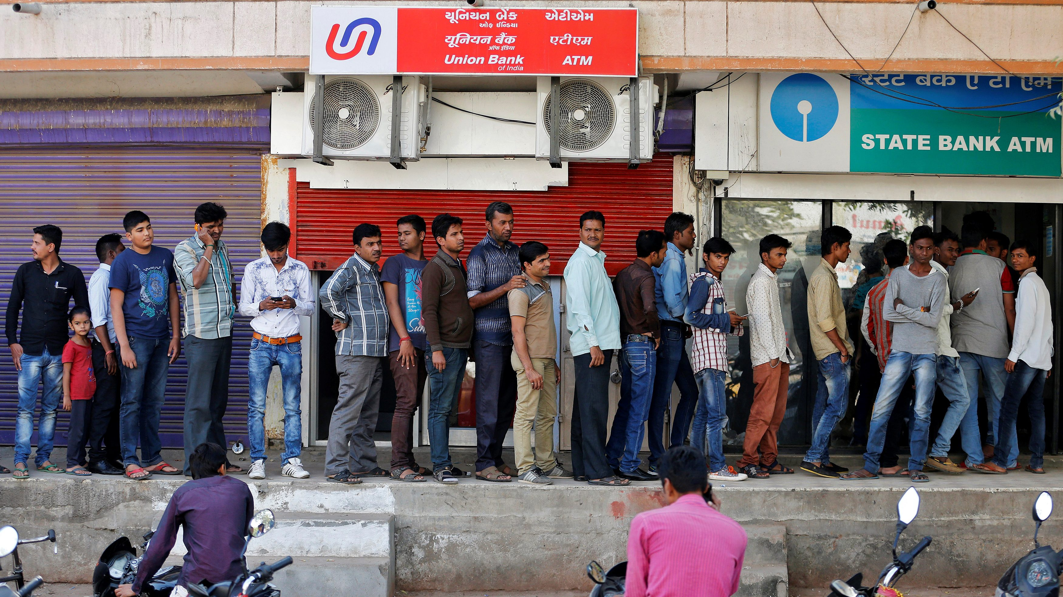 People queue outside an ATM of State Bank of India to withdraw cash in Ahmedabad, India, November 27, 2016.  - RC14158FB7F0