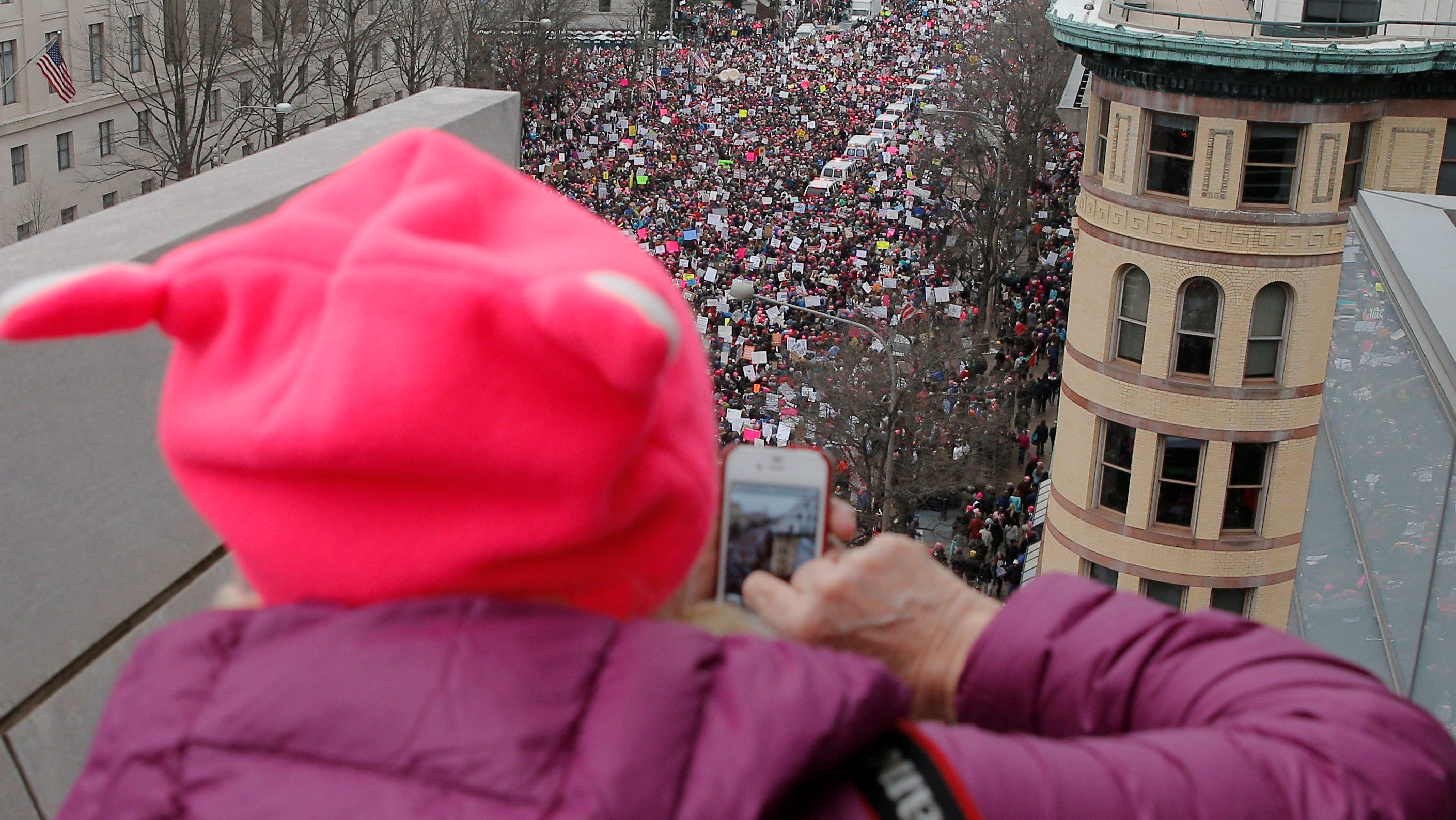 A woman wearing a pink pussy protest hat takes a photograph of the Women's March