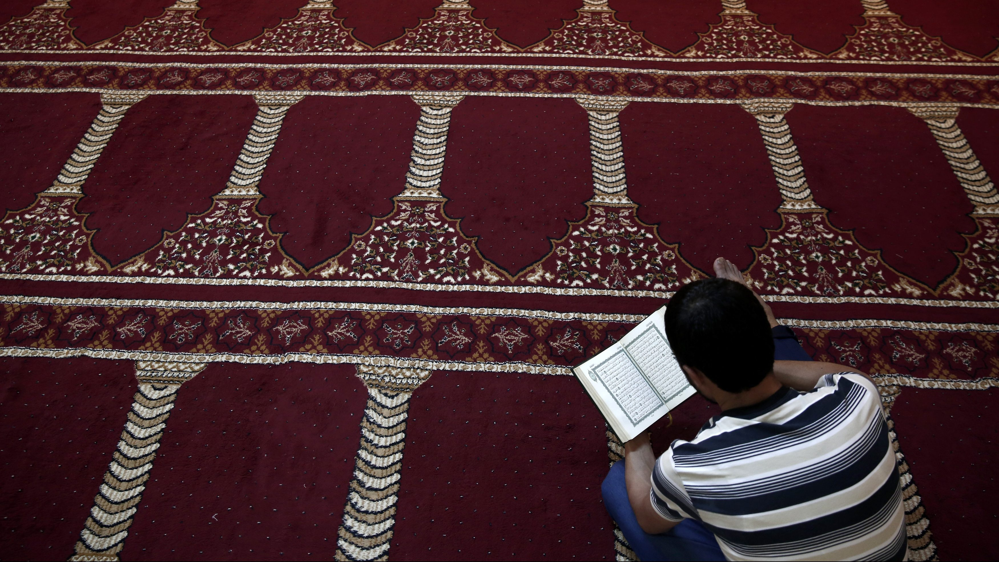 A Muslim faithful reads the Koran in Greece