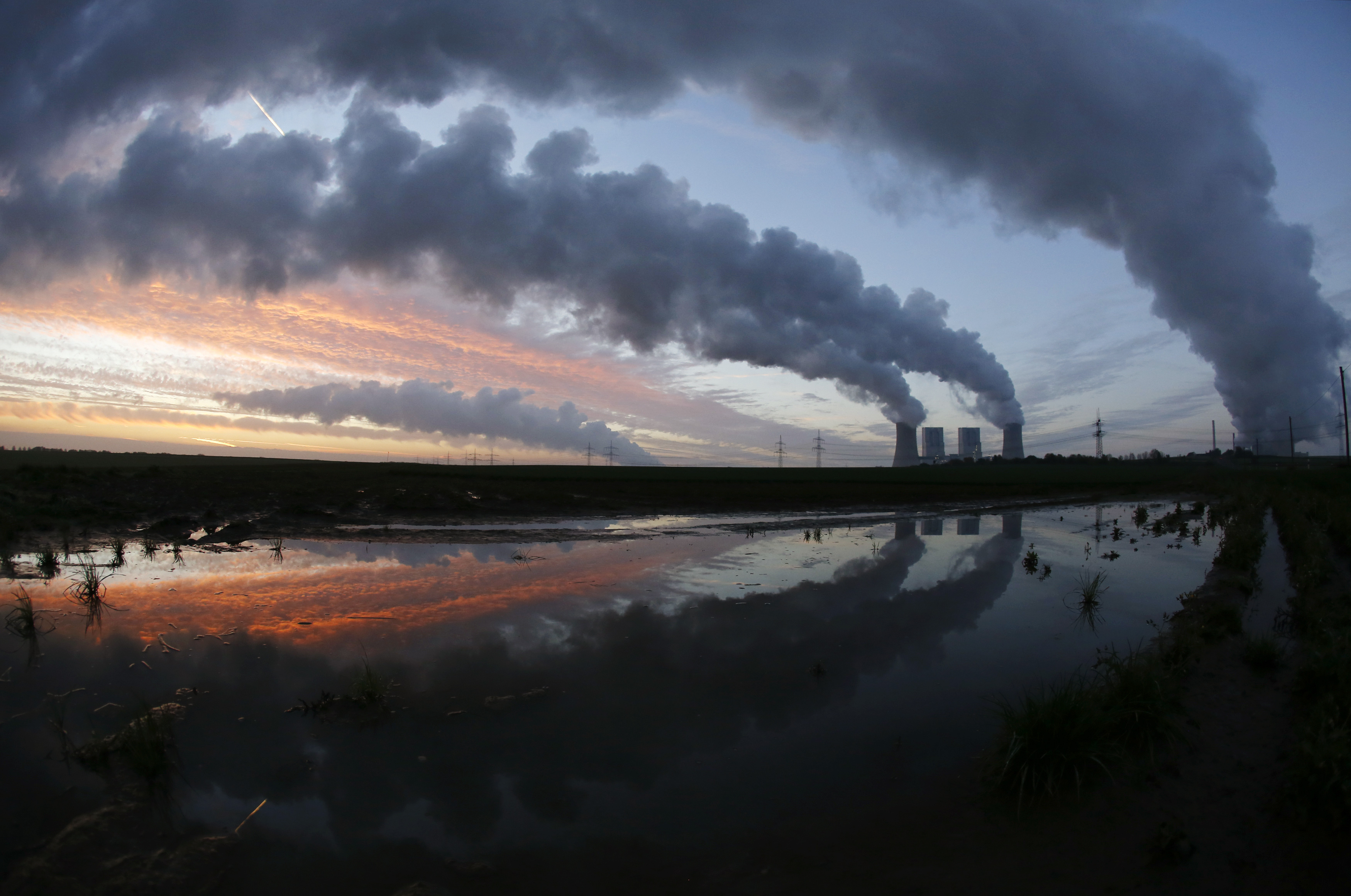 The coal power plant of German utility RWE Power is reflected in a puddle near the western town of Neurath November 14, 2013. RWE said it would cut more jobs and trim capital spending as it joined peers in warning of a deep crisis in Europe's energy industry that would keep a lid on growth in the foreseeable future. REUTERS/Ina Fassbender  (GERMANY - Tags: BUSINESS ENERGY EMPLOYMENT TPX IMAGES OF THE DAY) - GM1E9BE1DDZ01
