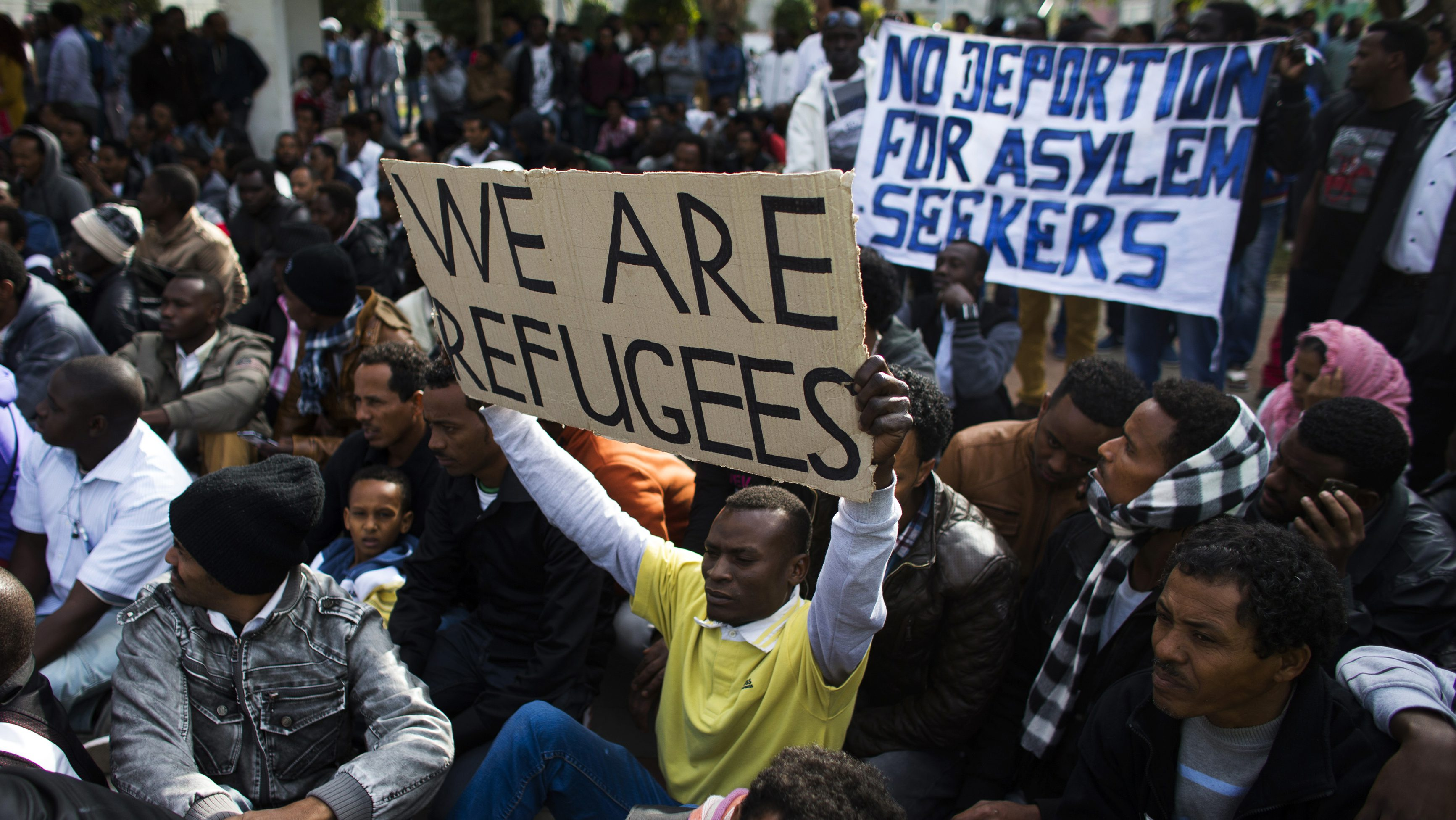 An African migrant holds up a sign as he sits with compatriots on the third day of protests against Israel's detention policy toward migrants it sees as illegal job-seekers, in Tel Aviv's Levinsky park January 7, 2014.