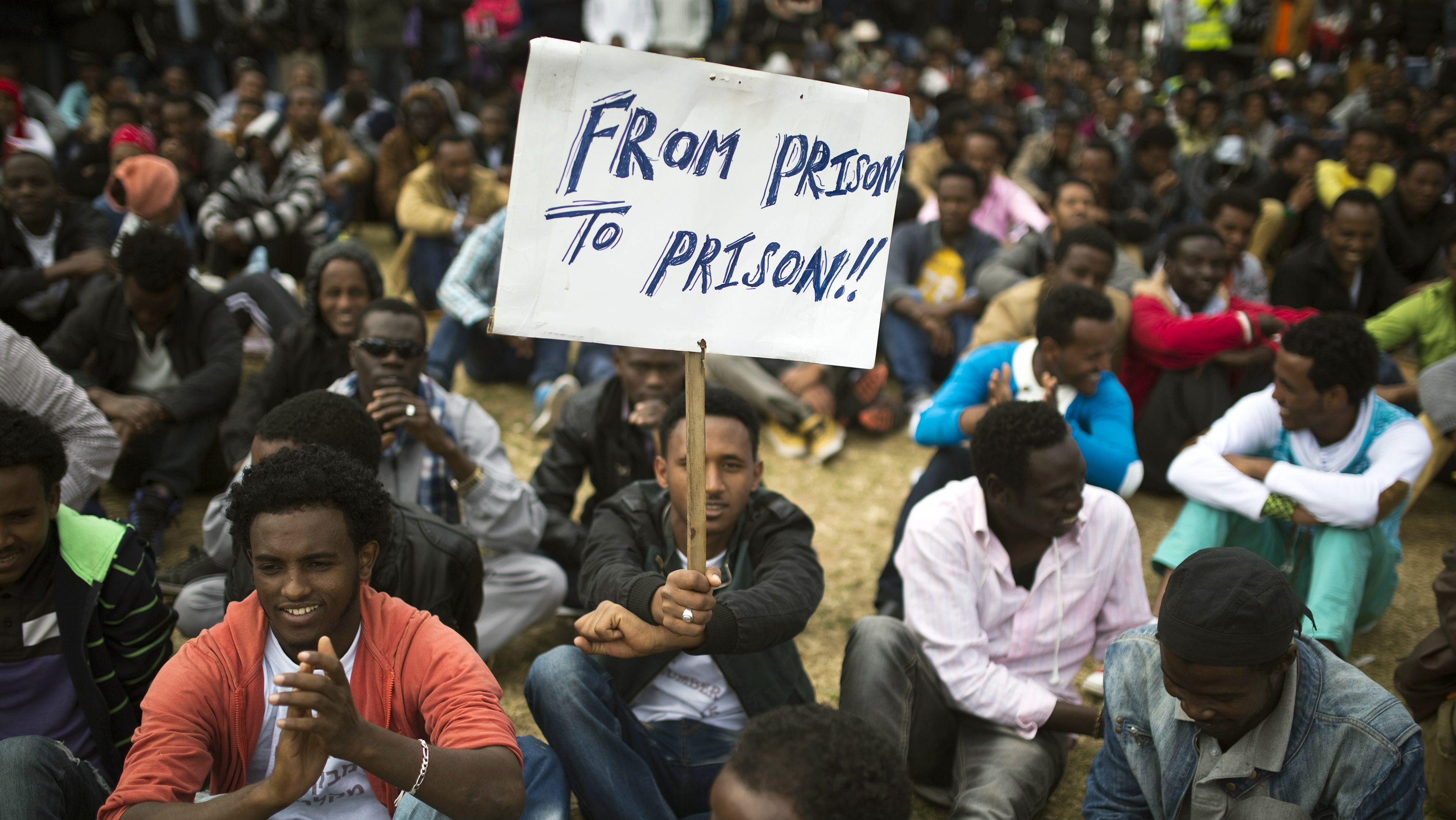 An African migrant holds a placard at Tel Aviv's Levinsky park, January 9, 2014, on the fifth consecutive day of protests against Israel's detention policy toward migrants it sees as illegal job-seekers. Israel passed a law three weeks ago allowing for indefinite detention of migrants without valid visas while it pursues efforts to persuade them to leave or enlist other countries to take them in.