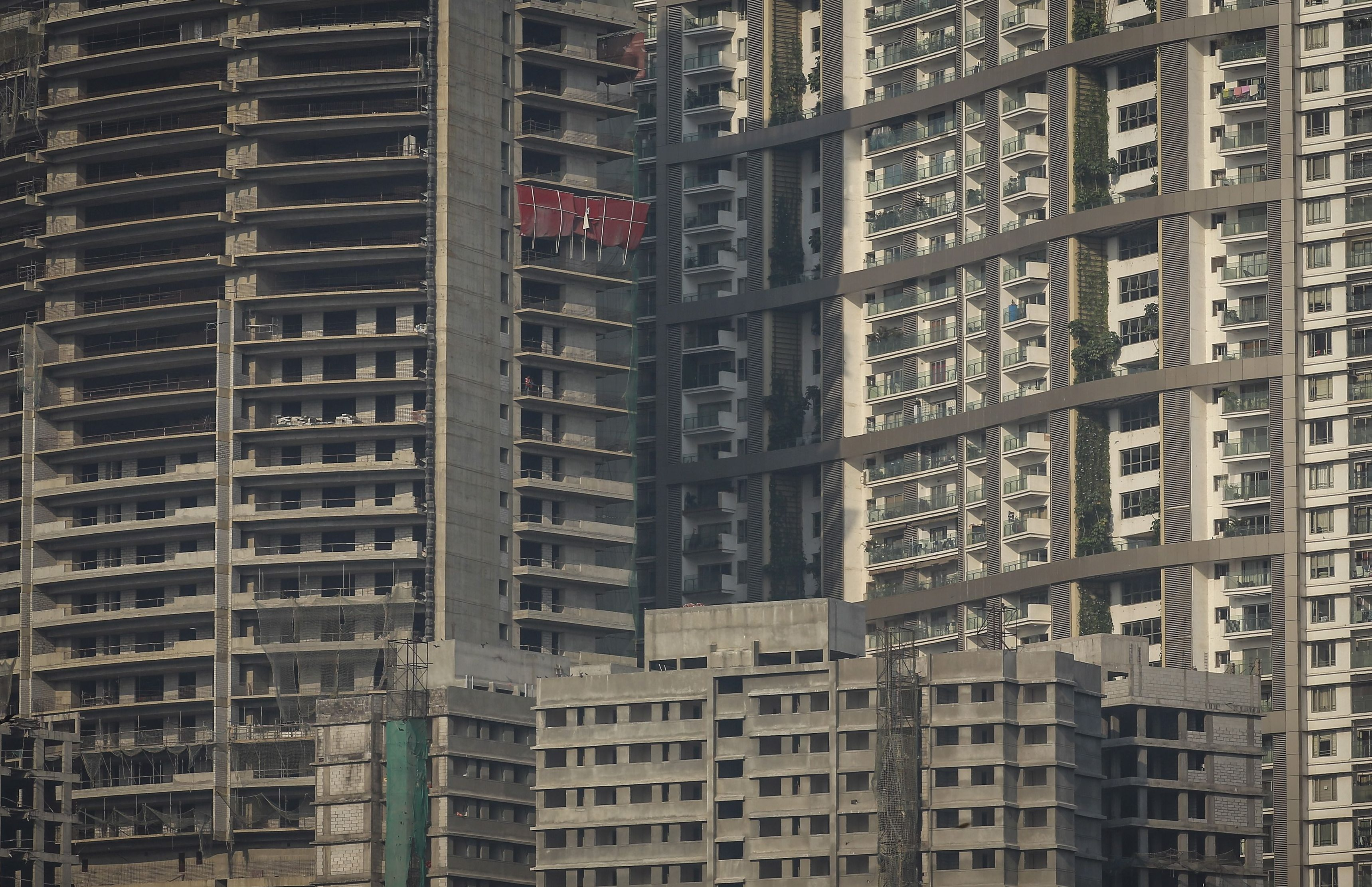 """Windows of high-rise residential buildings which are under construction are seen surrounding a residential tower (R) in central Mumbai January 12, 2015. The cost for buying a 2400 square feet (223 square meters) three-bedroom apartment in the completed residential tower is around 36,400 Indian rupees ($ 580) per square feet or 87,360,000 Indian rupees ($1.40 million). The rent for an apartment in the same building is around 150,000 Indian rupees ($ 2,400) per month. REUTERS/Danish Siddiqui  PICTURE 19 OF 22 FOR WIDER IMAGE STORY """"RENTING IN MUMBAI PER SQUARE FOOT""""?SEARCH """"RENTING SIDDIQUI"""" FOR ALL IMAGES? - GF10000068475"""