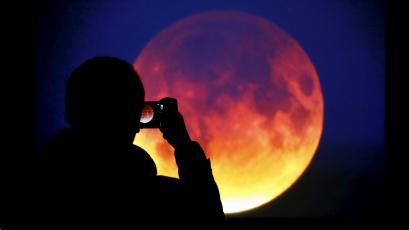 A man takes picture of the screen displaying the moon, appearing in a dim red colour, which is covered by the Earth's shadow during a total lunar eclipse in Warsaw, Poland September 28, 2015.
