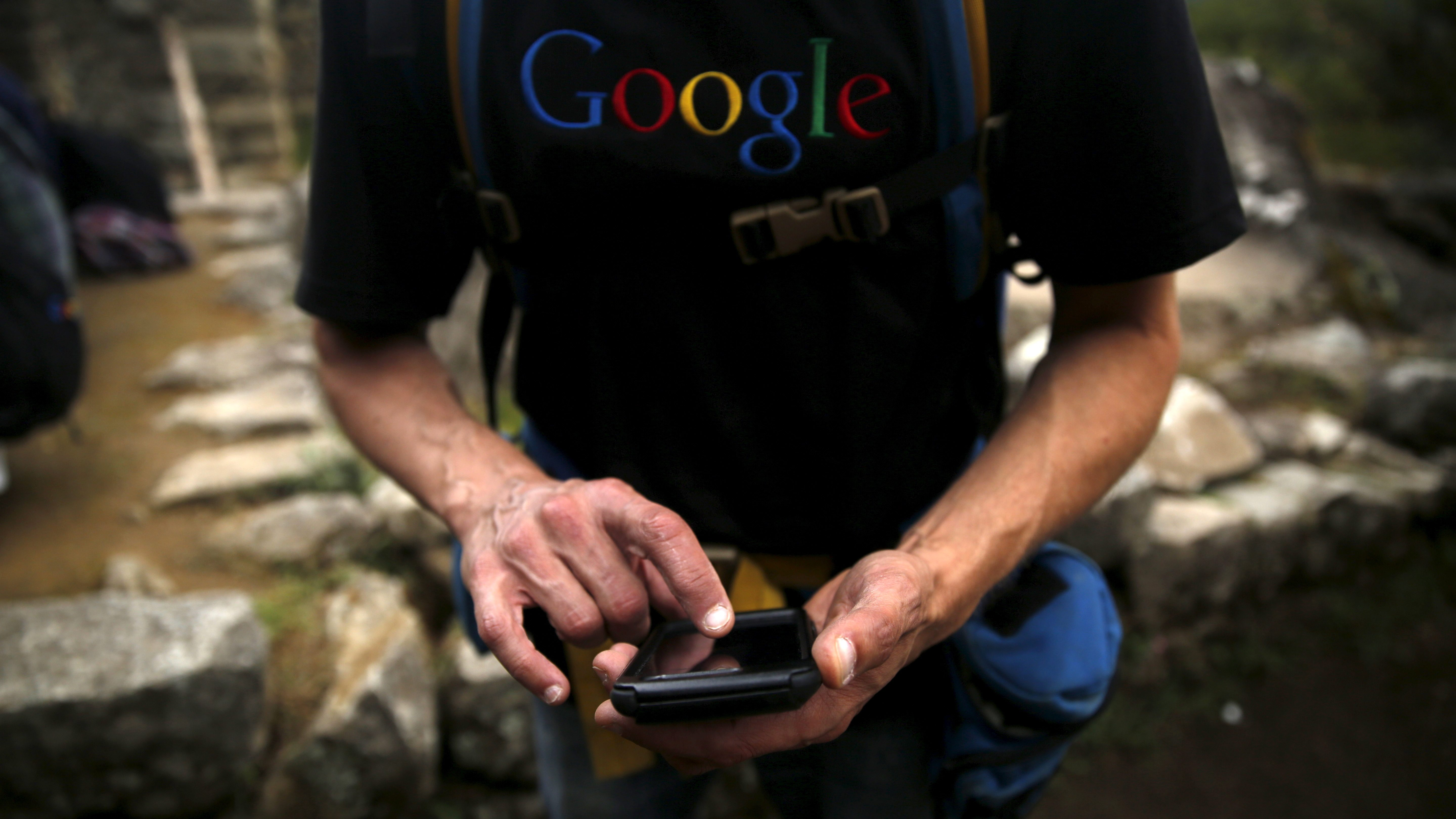 A man in a Google T shirt uses a phone.