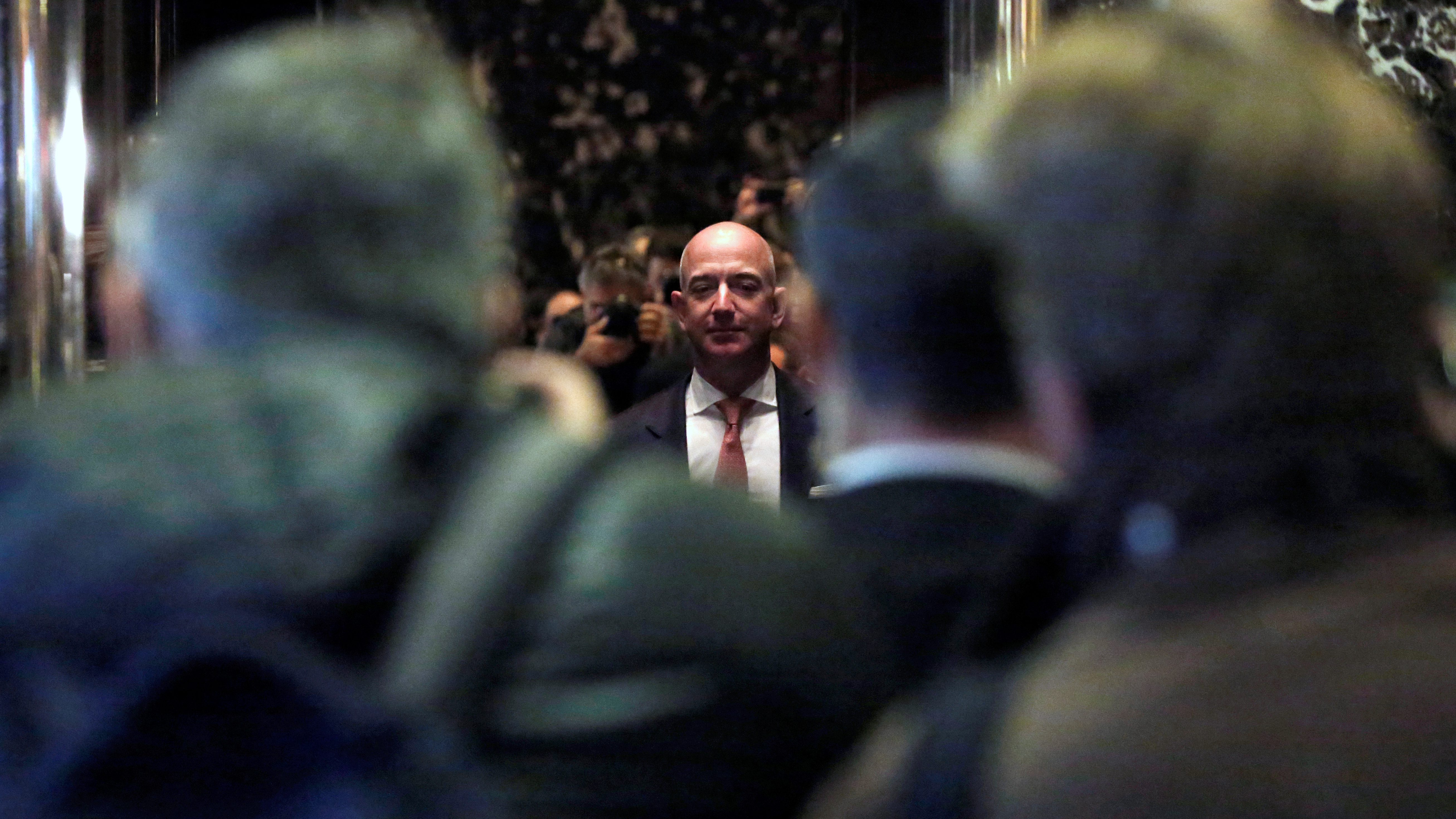 Jeff Bezos, founder, chairman, and chief executive officer of Amazon.com is photographed by media as he enters Trump Tower ahead of a meeting of technology leaders with President-elect Donald Trump in Manhattan, New York City, U.S.