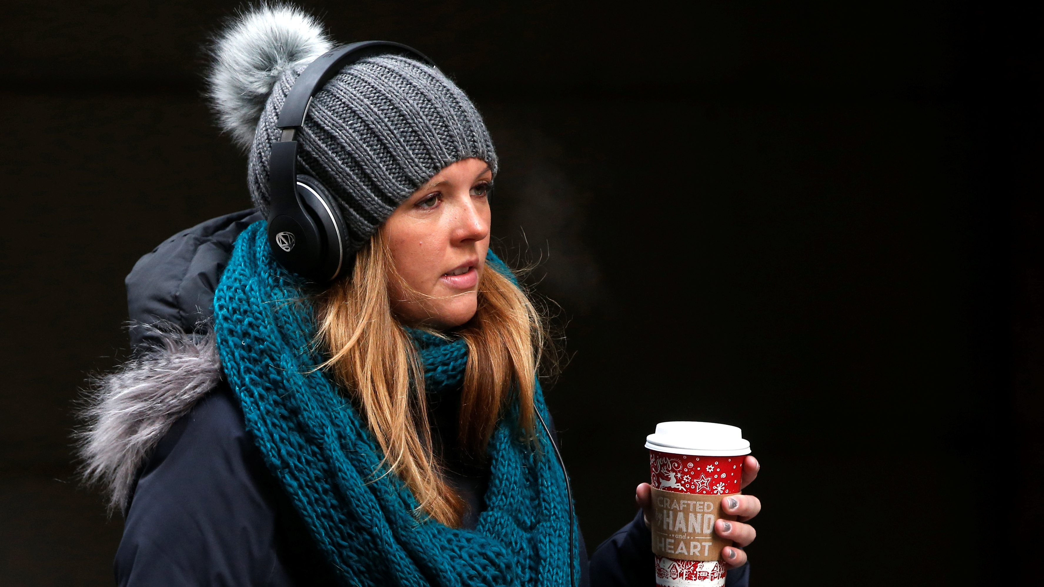 A woman walks bundled up from the cold on Wall St. during the morning commute in New York