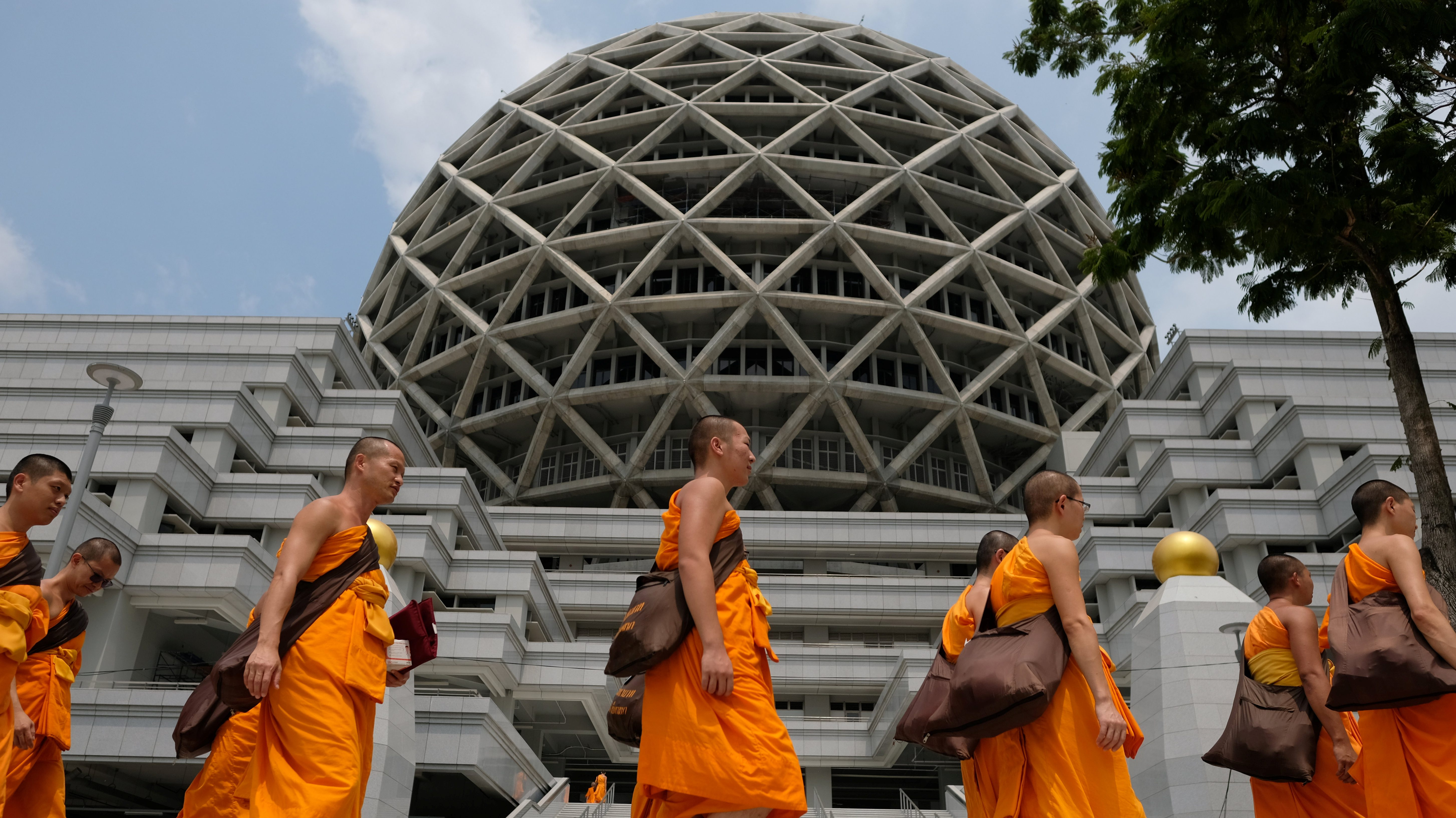 Buddhist Monks from Dhammakaya temple walk past a building inside Dhammakaya temple in Pathum Thani province, Thailand, March 9, 2017. Picture taken March 9, 2017. REUTERS/Athit Perawongmetha