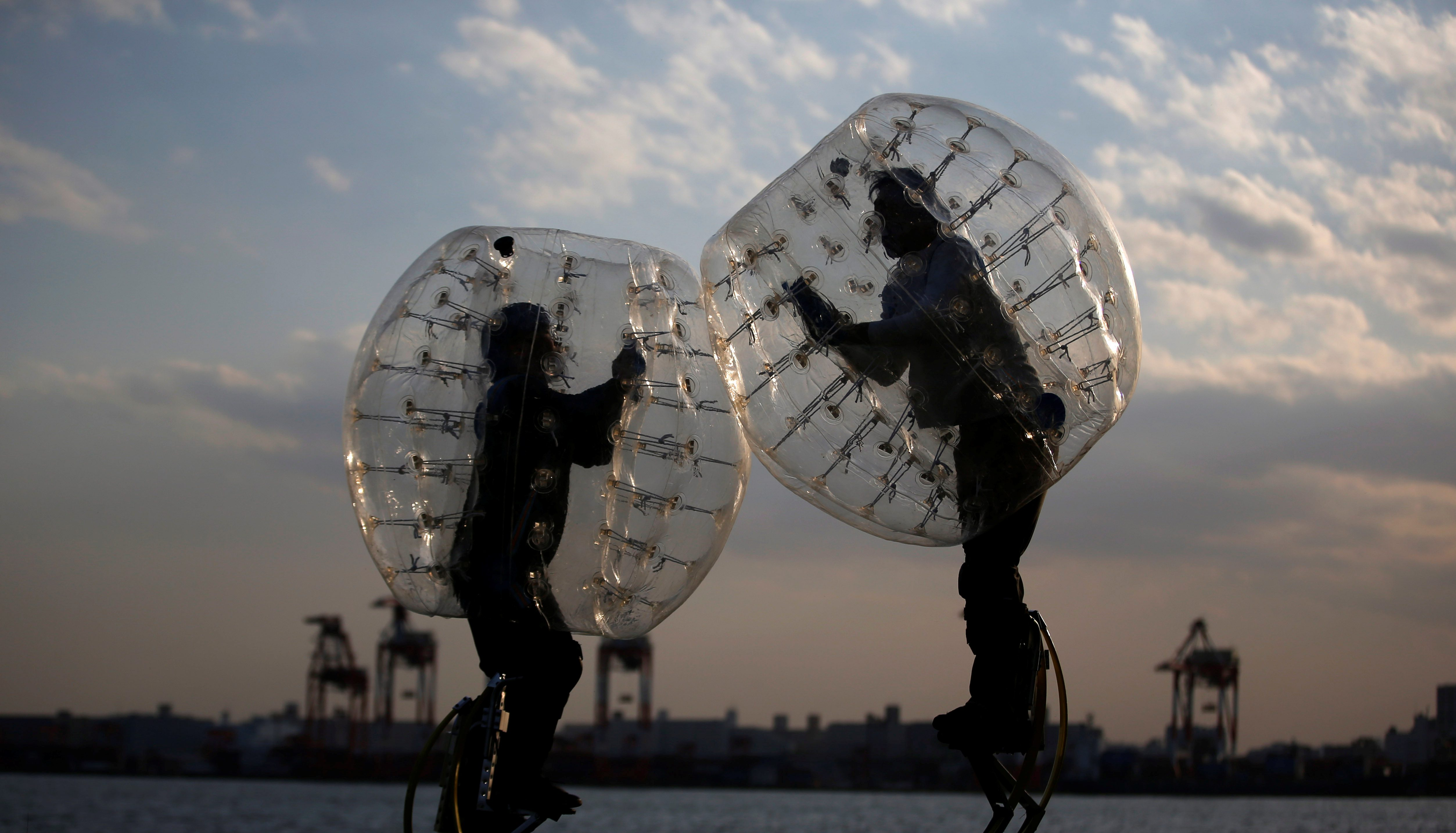 """Ryoichi Ando (R), 27, a virtual-reality researcher and an inventor of """"Bubble Jumper"""", competes with his opponent as they demonstrate the sport in Tokyo, Japan, April 13, 2017"""