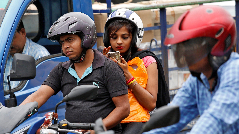 A woman checks her mobile phone at a traffic junction in Kolkata, India July 5, 2017. REUTERS/Rupak De Chowdhuri - RC17240A8A40