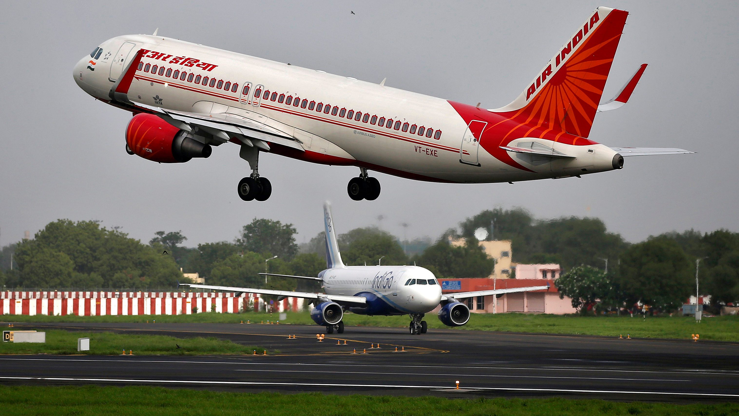 An Air India aircraft takes off as an IndiGo Airlines aircraft waits for clearance at the Sardar Vallabhbhai Patel International Airport in Ahmedabad, India, July 7, 2017. Picture taken July 7, 2017. To match Analysis AIR INDIA-PRIVATISATION/  REUTERS/Amit Dave - RC1DEE6C5CC0