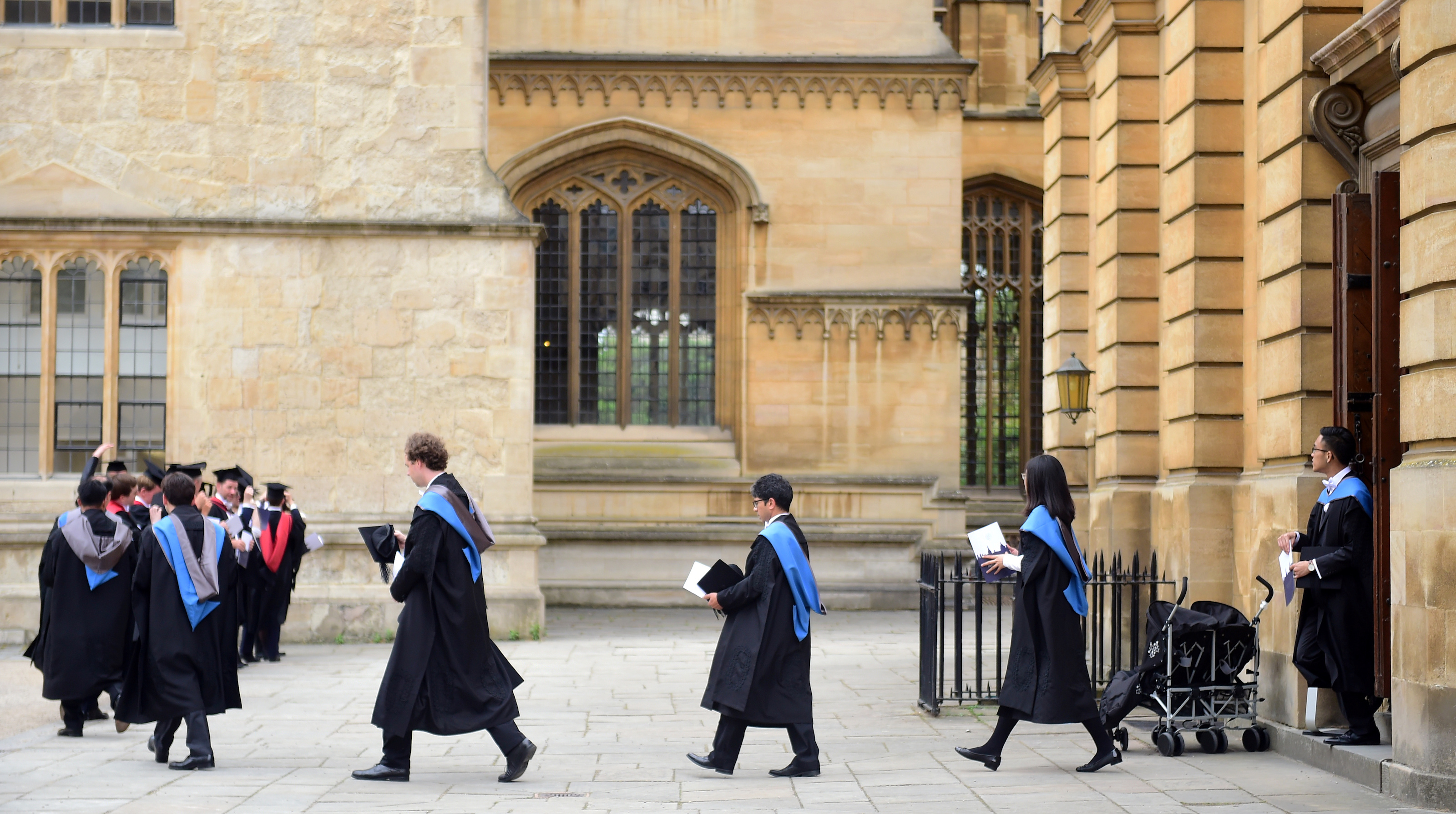 Graduates leave the Sheldonian Theatre after a graduation ceremony at Oxford University, in Oxford, Britain July 15, 2017. REUTERS/Hannah McKay - RC12AE521EB0