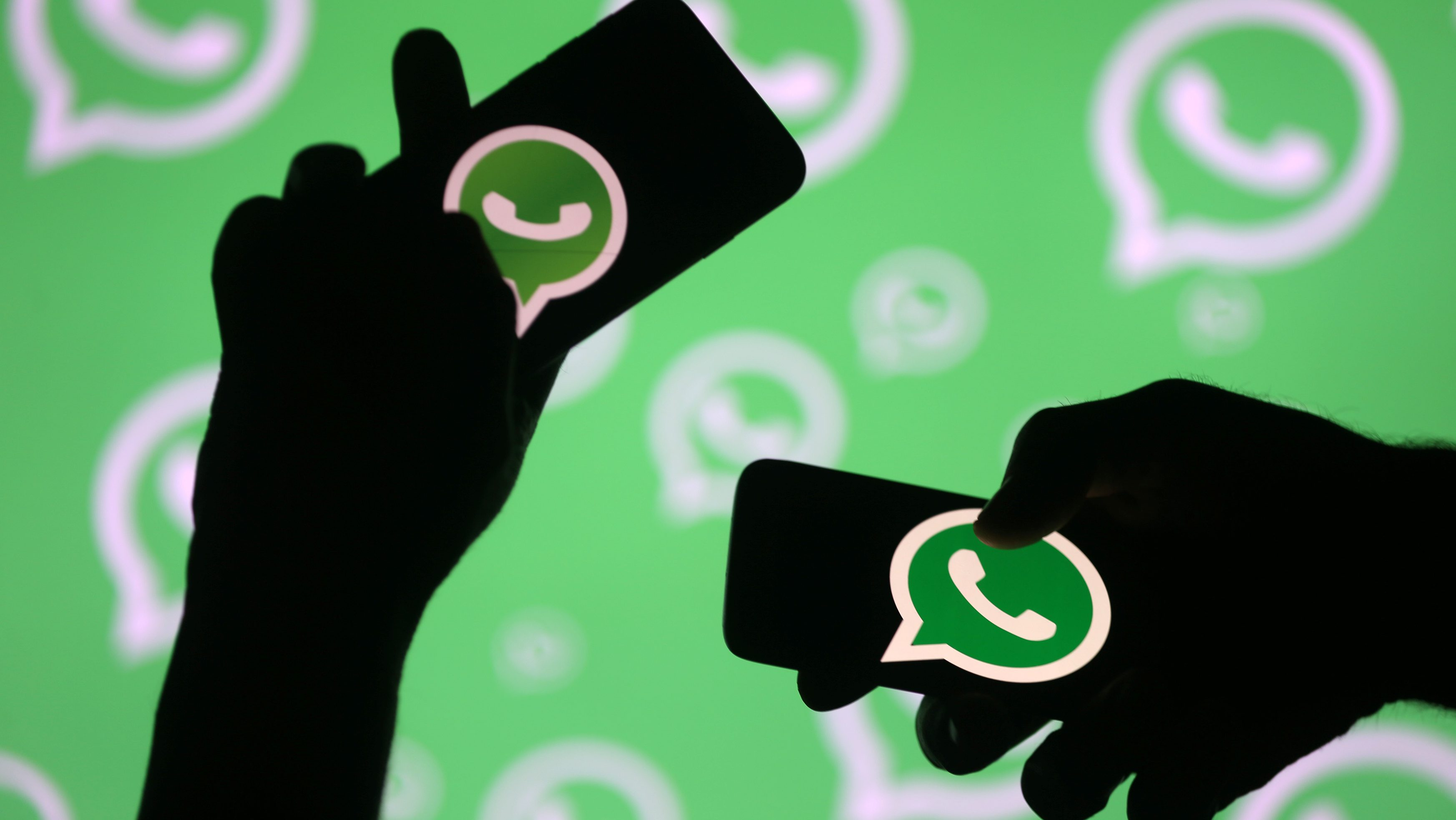 Men pose with smartphones in front of displayed Whatsapp logo in this illustration