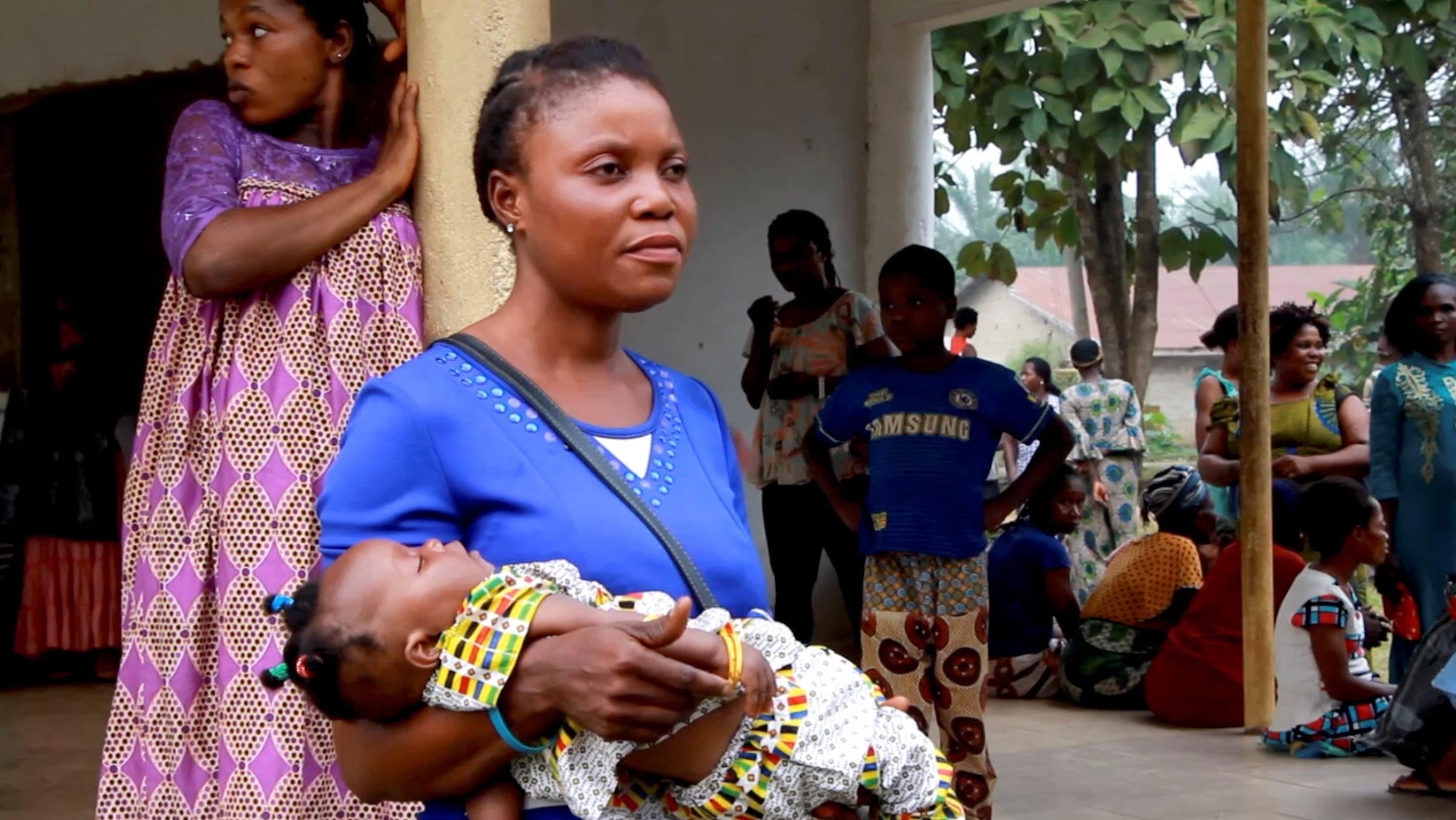 A still image taken from a video shot on December 9, 2017 shows a Cameroonian refugee woman carrying a child outside a center in Agbokim Waterfalls village, which borders on Cameroon, Nigeria.