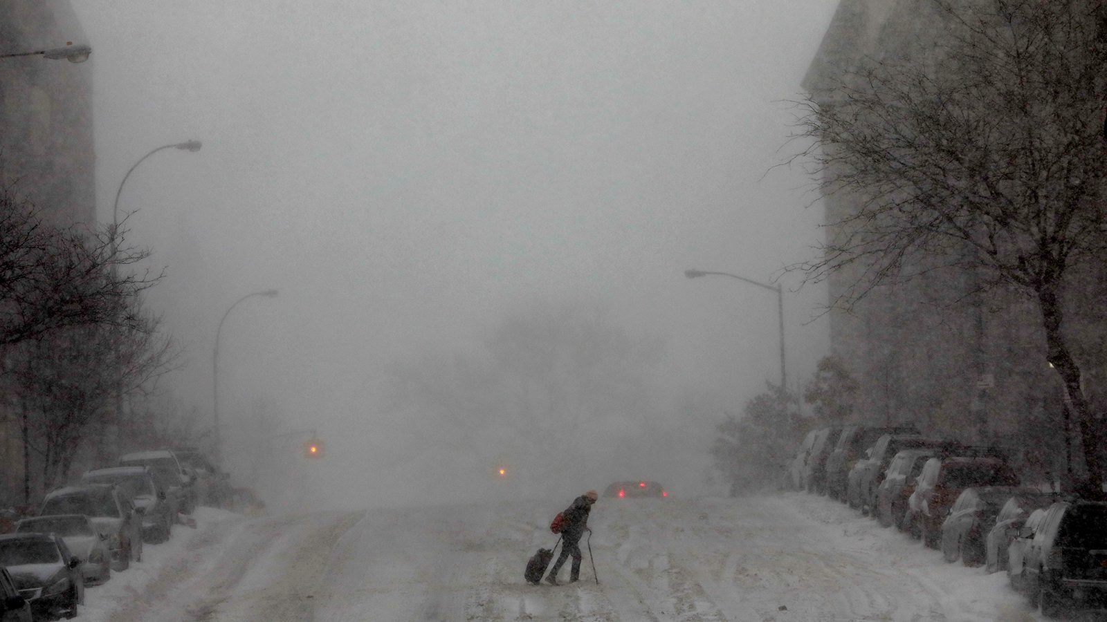 A woman struggles across a snow-covered 145th Street in upper Manhattan during a snowstorm in New York City