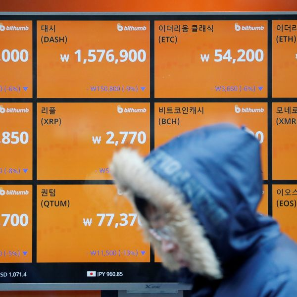A man walks past an electric board showing exchange rates of various cryptocurrencies at Bithumb cryptocurrencies exchange in Seoul, South Korea, January 11, 2018.