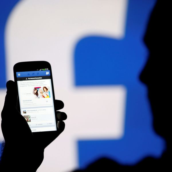 FILE PHOTO: A man is silhouetted against a video screen with an Facebook logo as he poses with an Samsung S4 smartphone in this photo illustration August 14, 2013. REUTERS/Dado Ruvic/File Photo - RC172F69CDF0