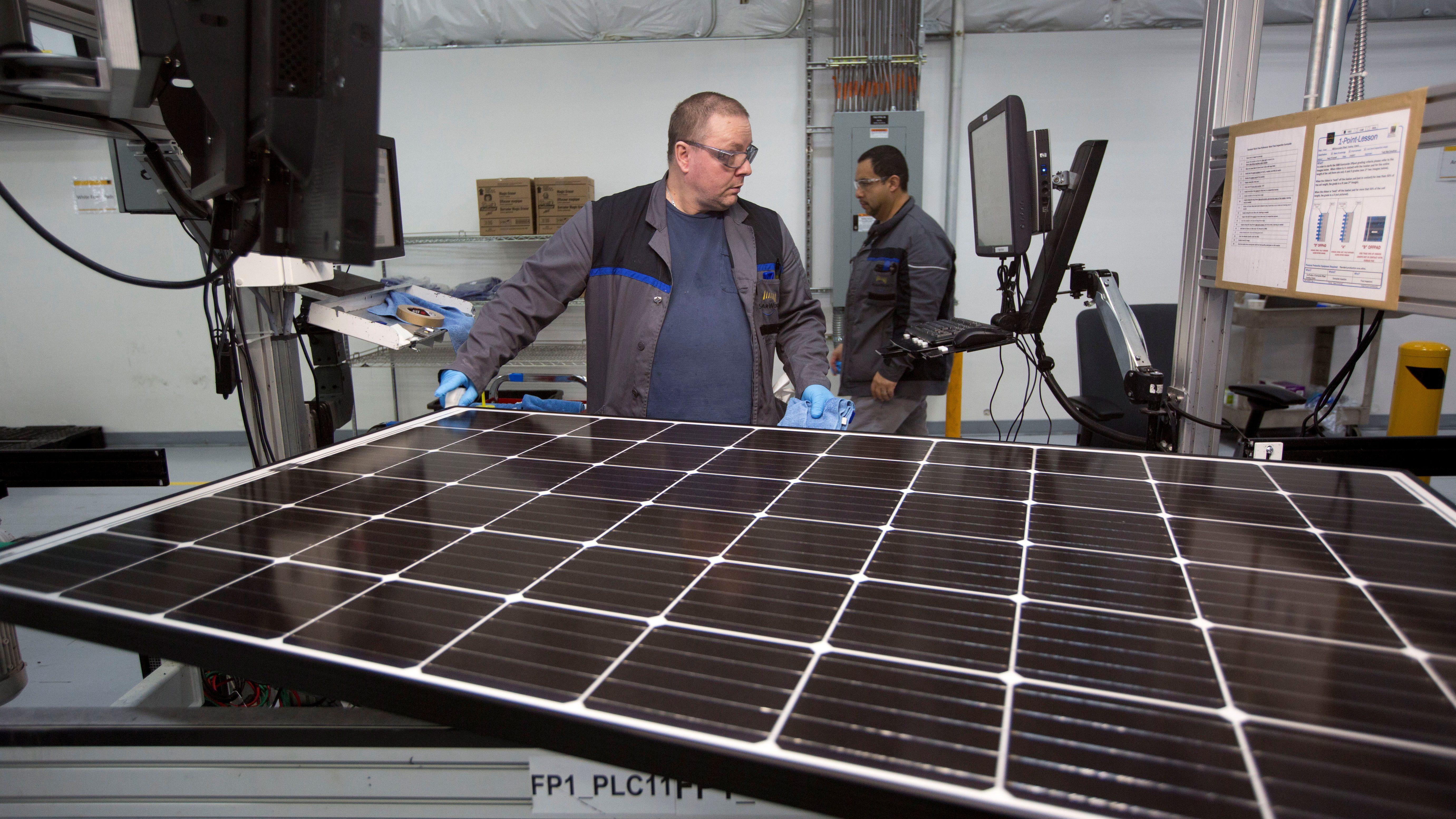 Production operator John White checks a panel at the SolarWorld solar panel factory in Hillsboro, Oregon, U.S., January 15, 2018. Picture taken January 15, 2018.  - RC1A2904F740