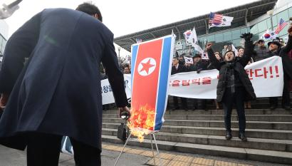 A member of a South Korean conservative civic group burns a North Korean national flag during a protest opposing North Korea's participation in the 2018 Pyeongchang Winter Olympics, in Seoul