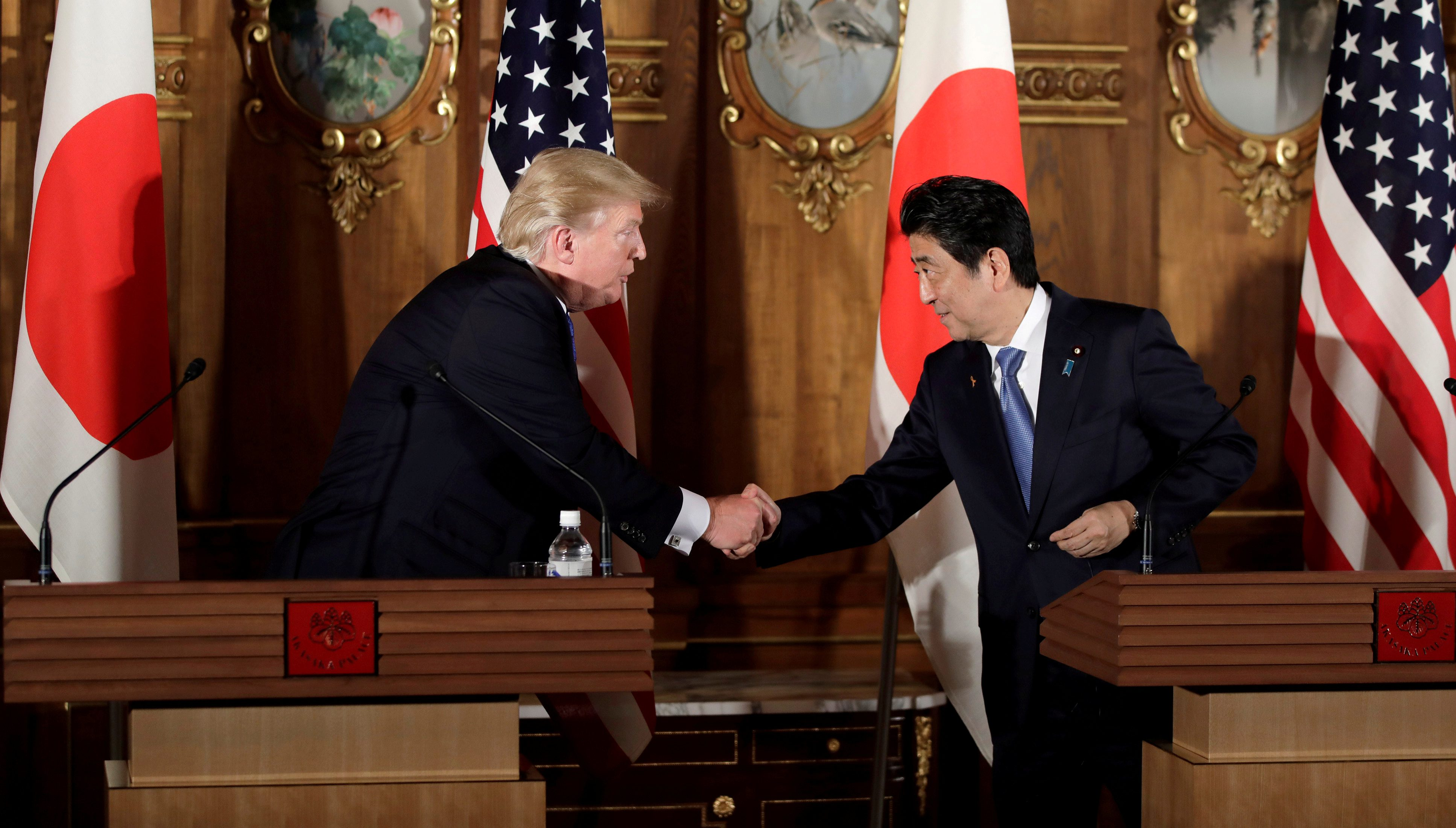 Donald Trump (L) shakes hands with Japan's Prime Minister Shinzo Abe during a news conference at Akasaka Palace in Tokyo, Japan, November 6, 2017. REUTERS/Kiyoshi Ota/Pool/File Photo - RC1EA05BE1C0