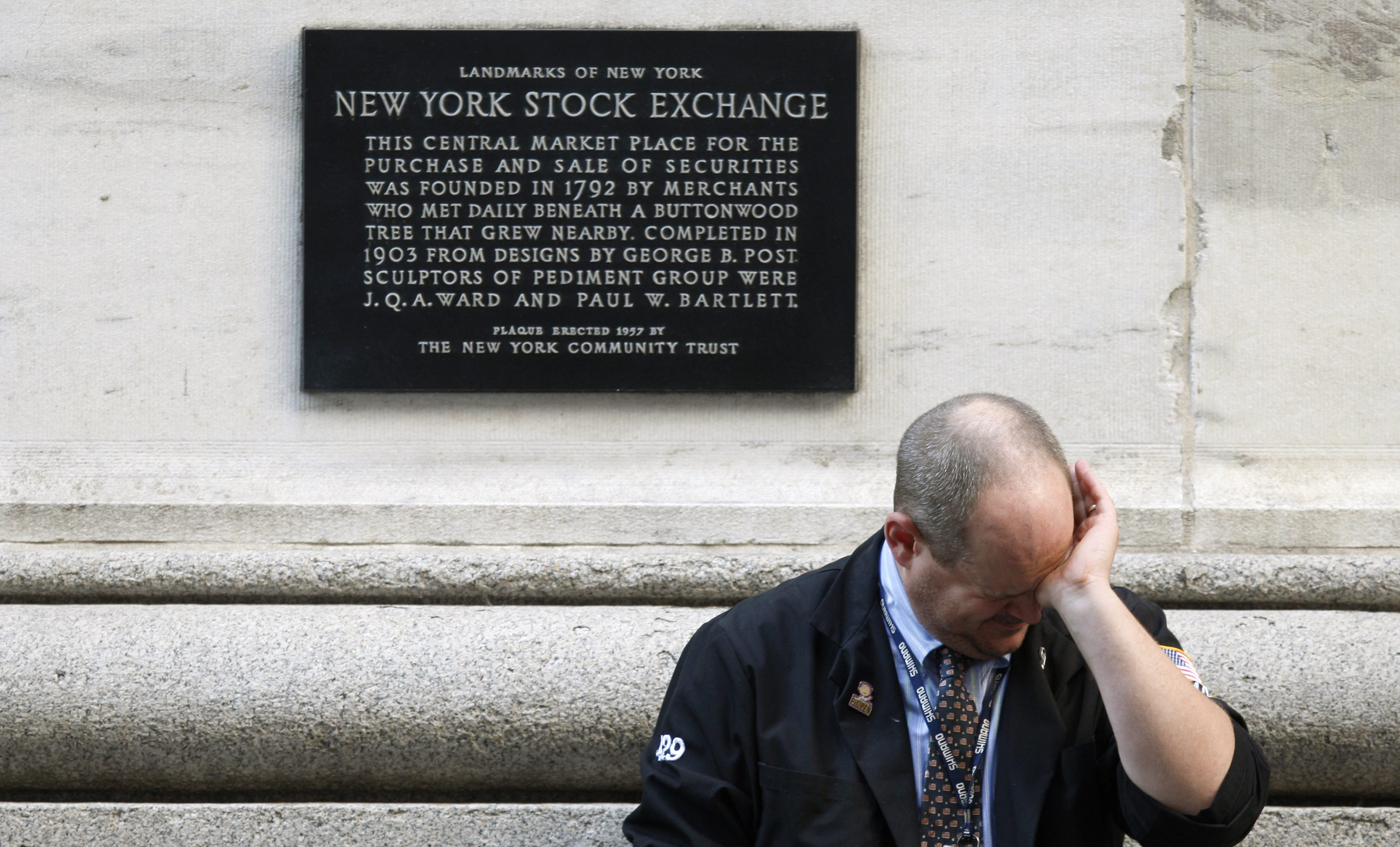 A weary trader rubs his eyes as he pauses outside the New York Stock Exchange following the end of the trading session in New York October 9, 2008. The Dow Jones Industrial Average dropped 678.91 points on the day to finish at 8579.19 closing below 9,000 for the first time since 2003.