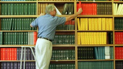Man pulling books from a library shelf