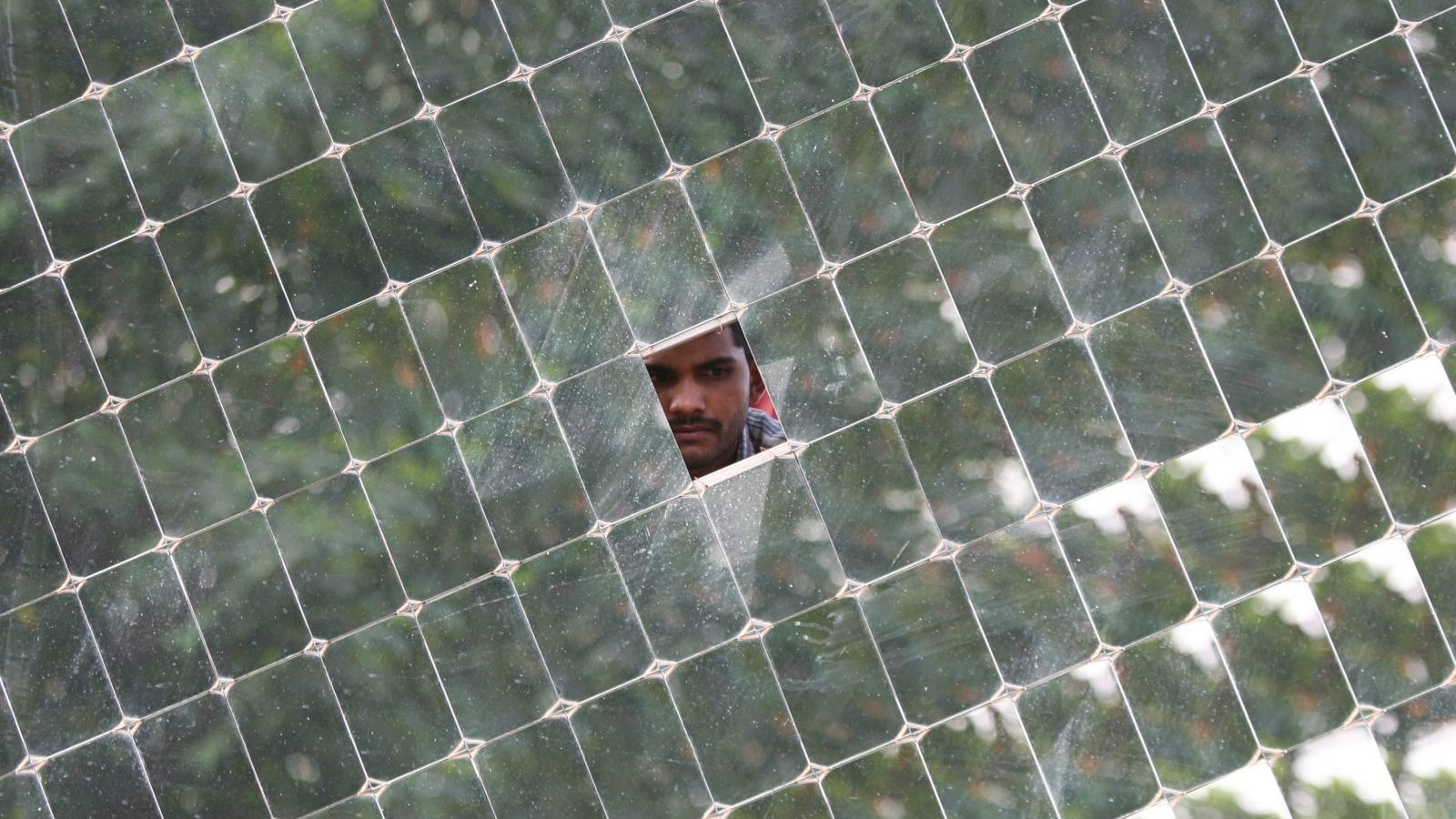 A worker looks through a solar concentrator panel (solar parabolic dish) at the Gadhia solar energy systems manufacturing unit at Gundlav village, about 400 km (250 miles) south of the western Indian city of Ahmedabad, December 16, 2009. REUTERS/Amit Dave (INDIA - Tags: ENERGY ENVIRONMENT EMPLOYMENT BUSINESS) - GM1E5CH0AS001