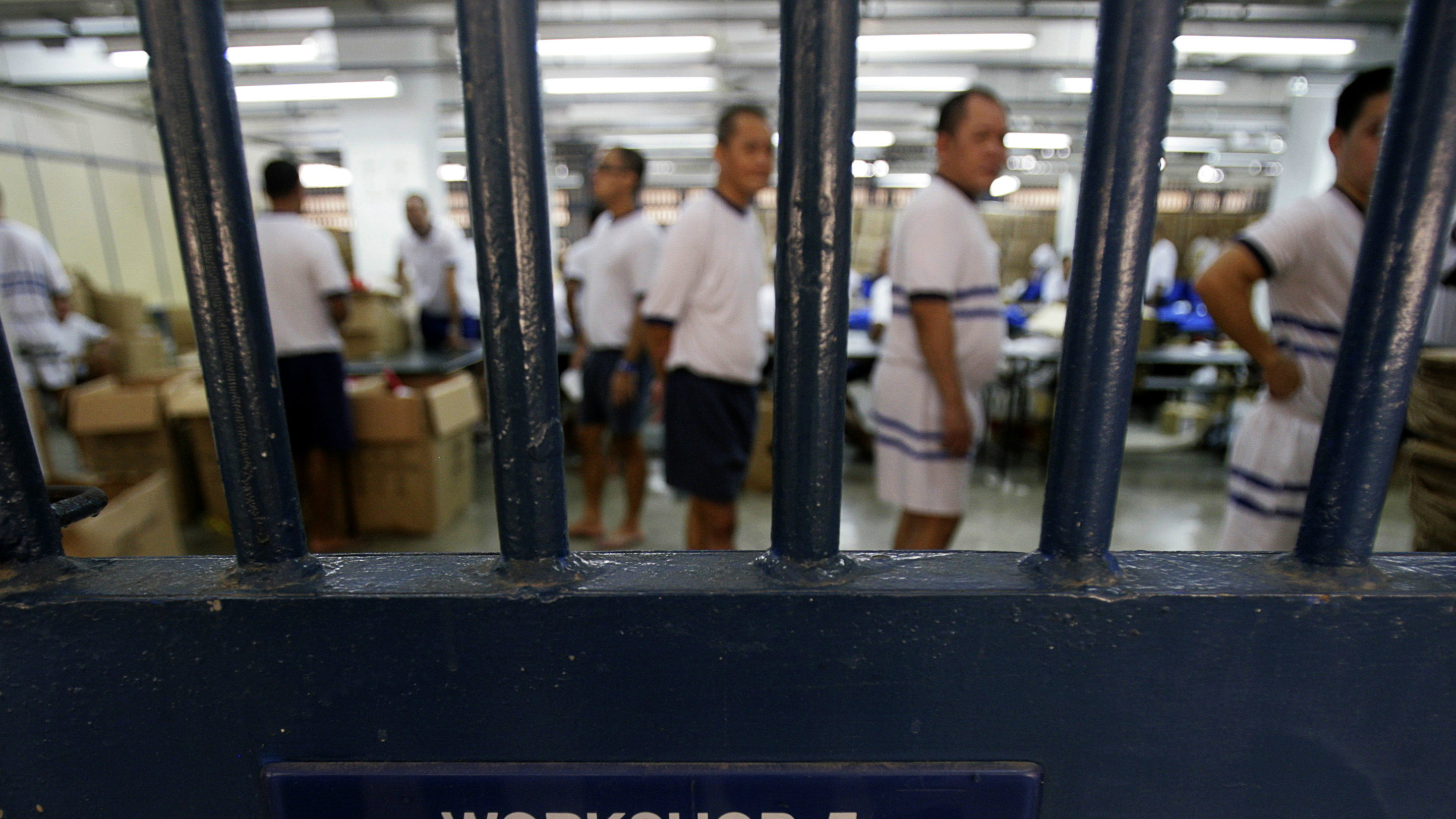 Inmates are seen behind the bars on a gate to a workshop at Sinapore's Tanah Merah Prison June 23, 2009. The inmates have been preparing goodie bags to be given away to spectators at this year's National Day Parade, as part of the Yellow Ribbon Project which aims to tackle negative community attitudes towards people who have served time in Singapore's prisons.